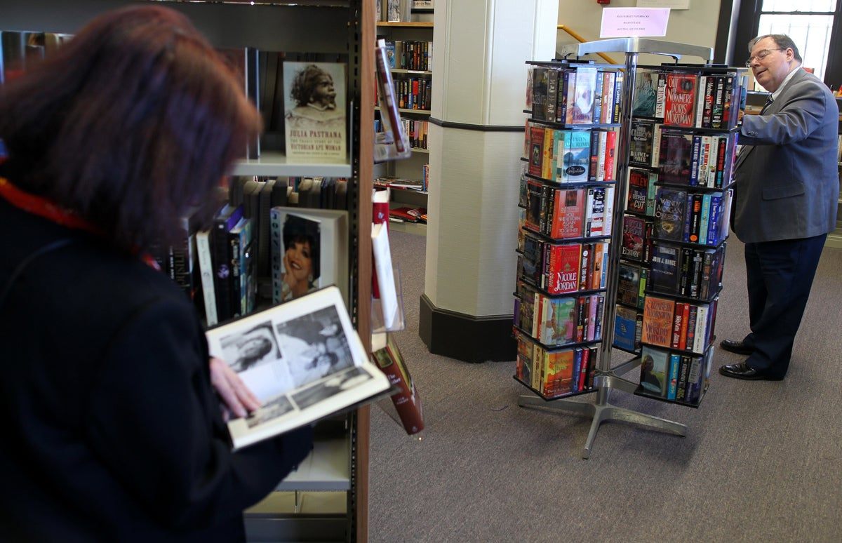 Library director Harry R. Williams III looks over the titles at the bookstore that opened last fall at the Thomas Crane Public             Library in Quincy. Used books are priced between 50 cents and $2.