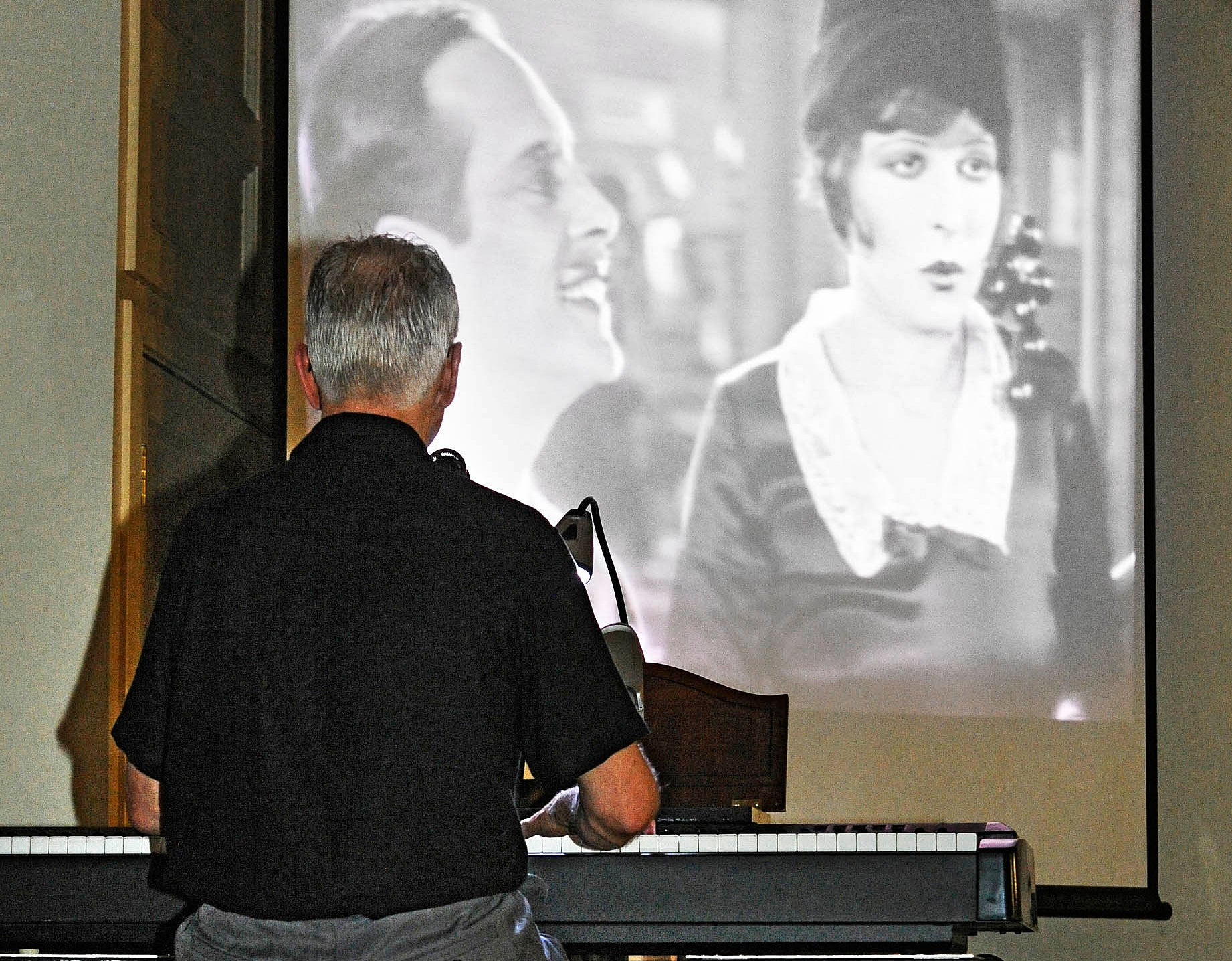 Hudson resident Richard Hughes provides the musical accompaniment for the 1927 silent film It, featuring Clara Bow, for             a recent community gathering in Stows Old Town Hall.
