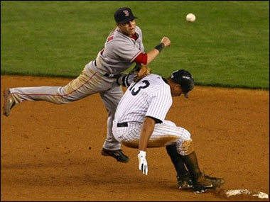 Dustin Pedroia of the Red Sox threw to first base as Alex Rodriguez of the New York Yankees broke up the double play in the eighth inning at Yankee Stadium last night