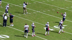 Tom Brady warms up with a toss to Deion Branch
