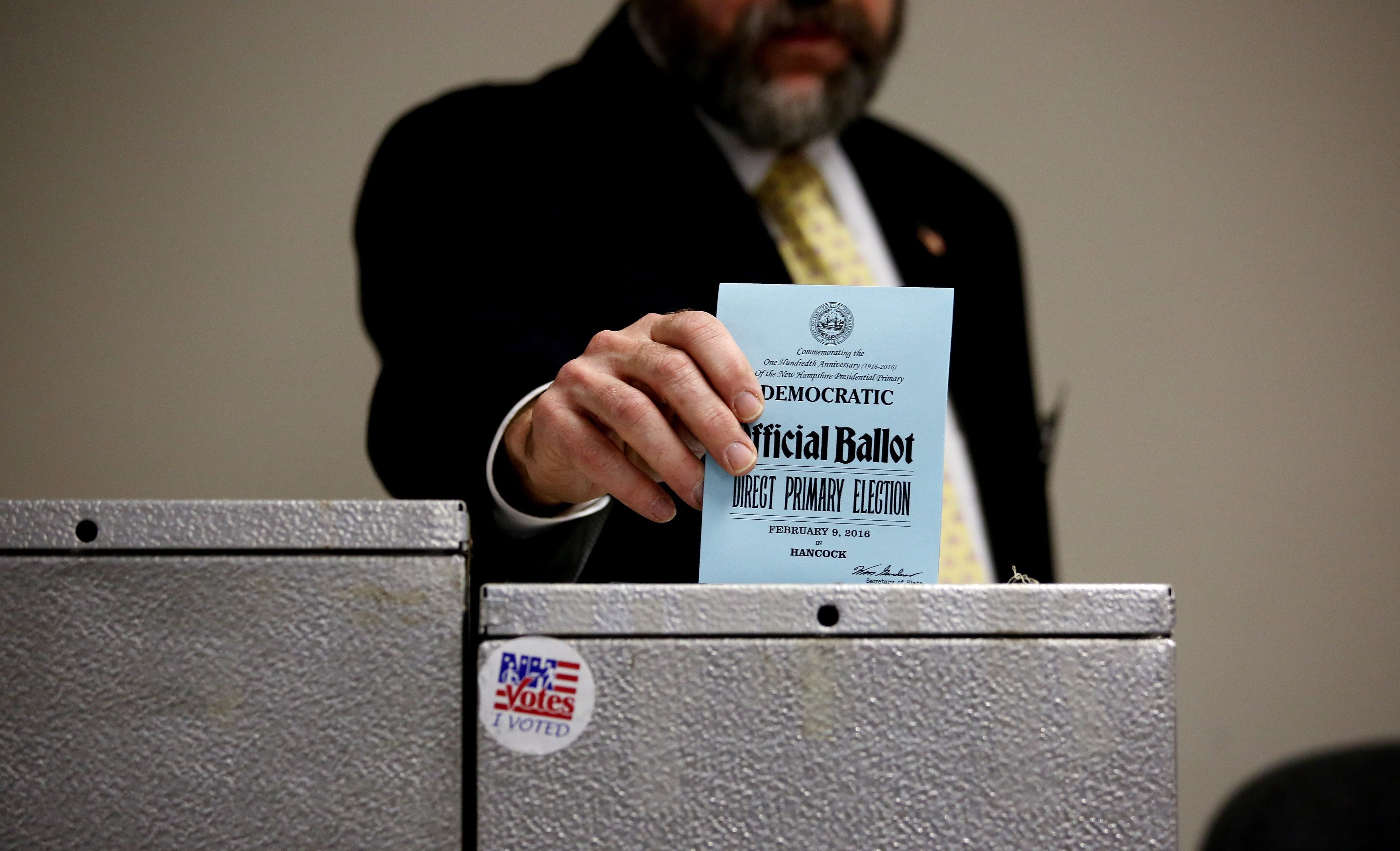 Town Moderator Richard Haskins enters his ballot in today's presidential primary in Hancock, New Hampshire.