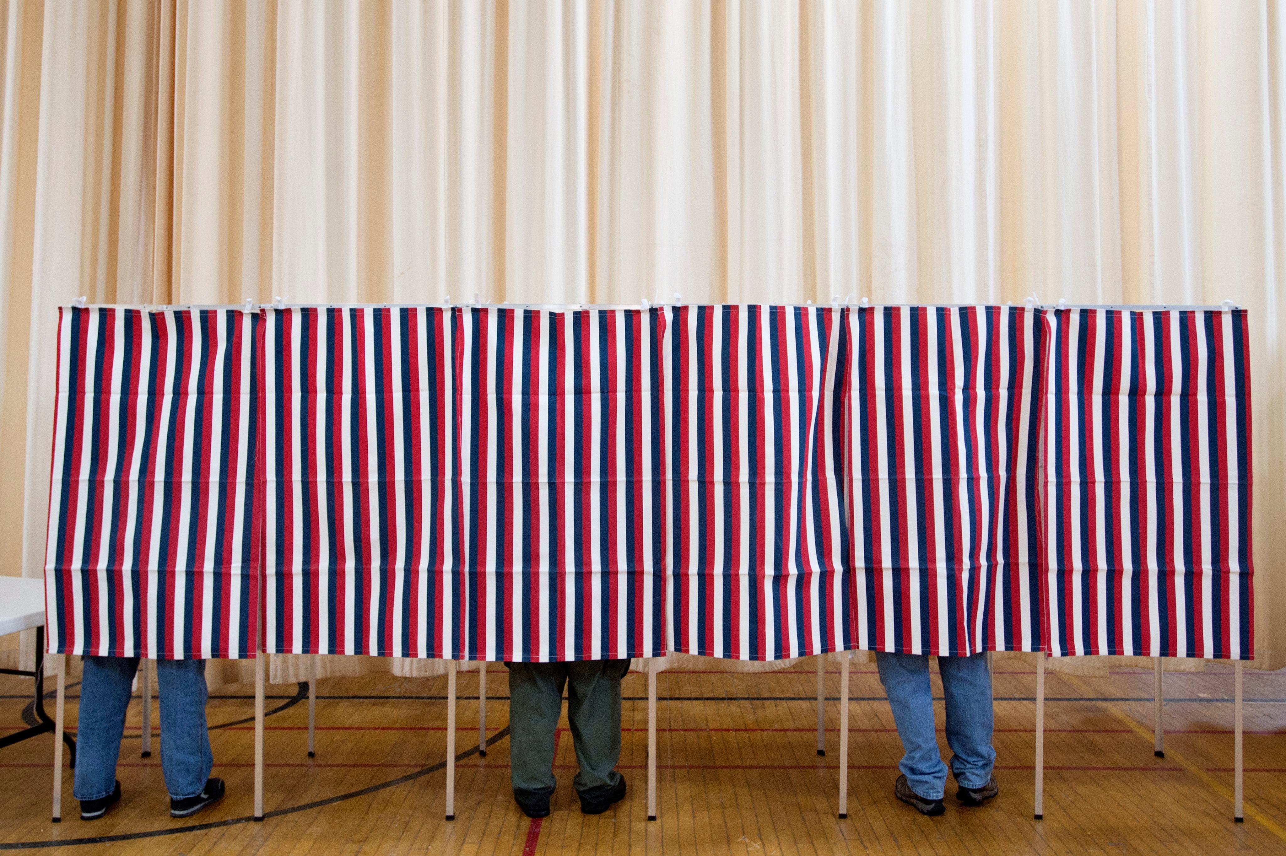 People stand in booths to vote in the New Hampshire primary at a polling station in Laconia, New Hampshire.