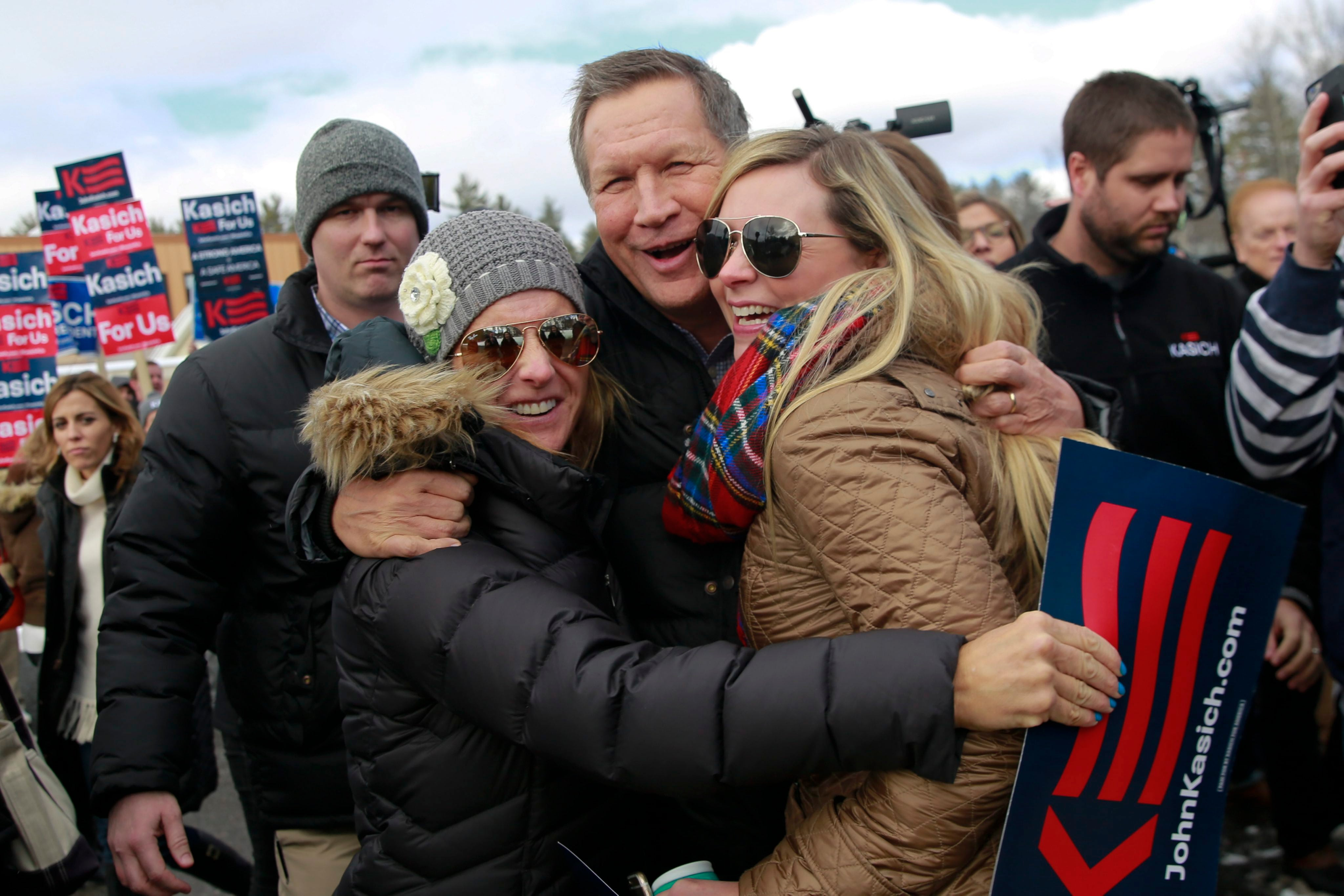 Kasich hugs Annmarie Vermeer (L) and Miranda Yeaton (R) outside a polling station in Concord, New Hampshire.