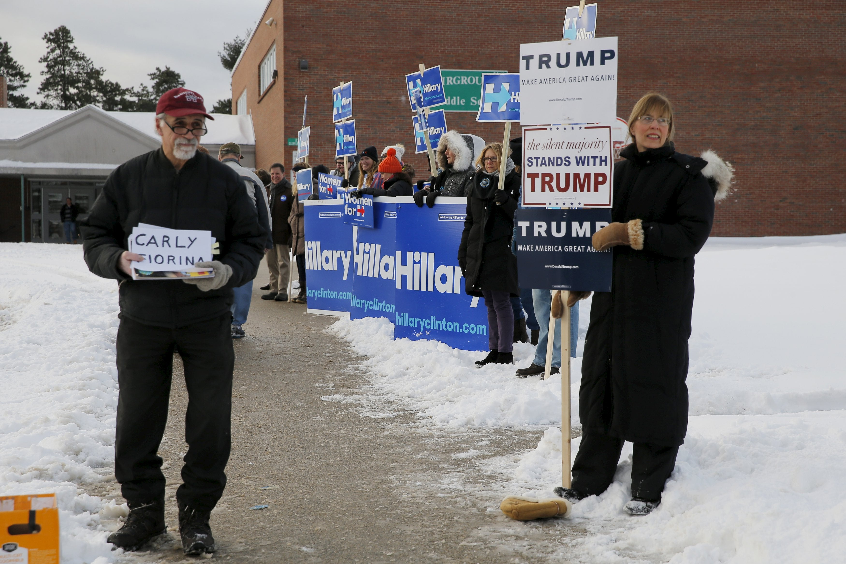 Supporters of presidential candidates Carly Fiorina and Donald Trump stand outside a polling place alongside supporters of Hillary Clinton in Nashua, New Hampshire.
