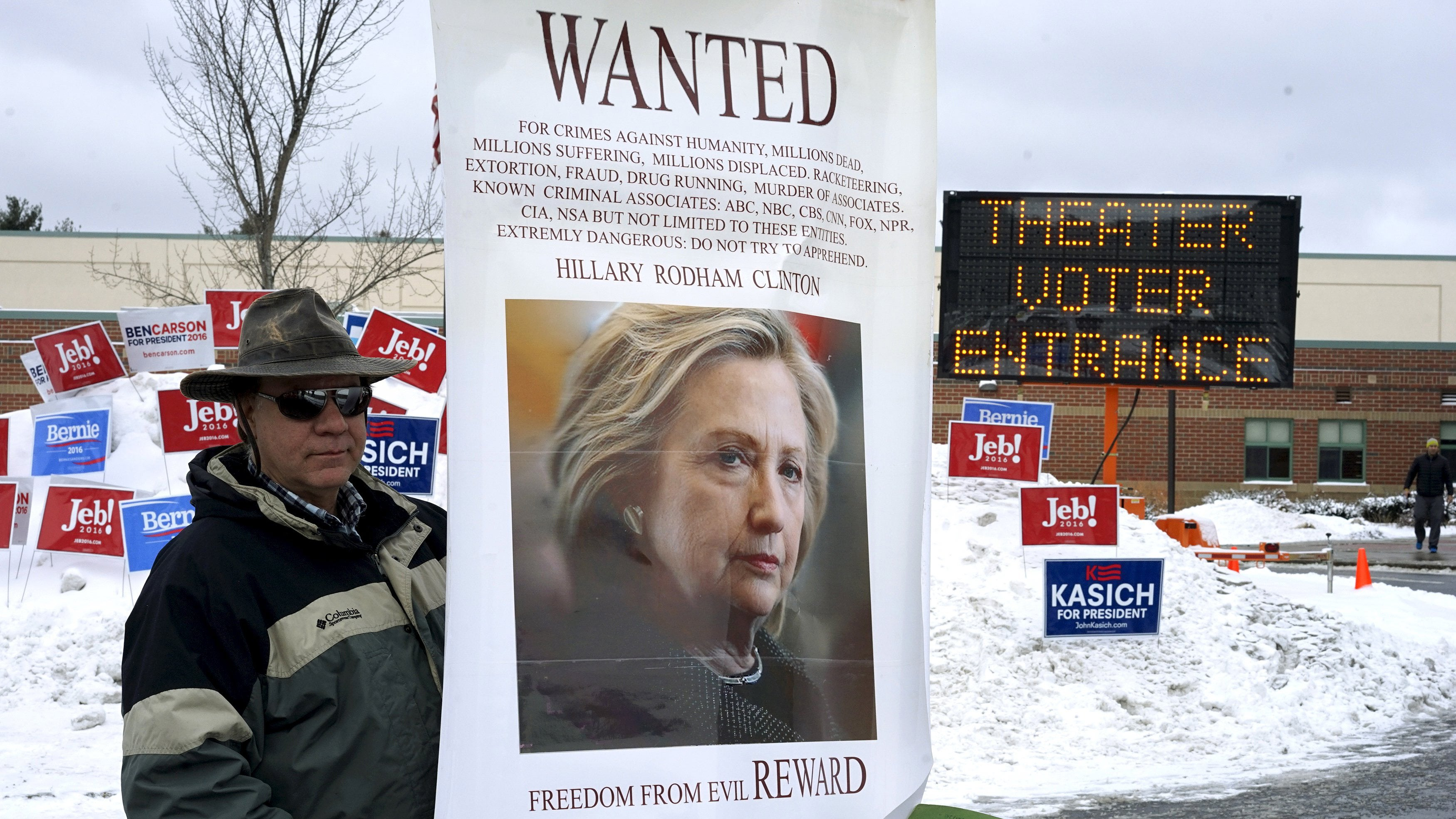 A protestor stands outside the entrance to the polling place for the presidential primary at Bedford High School in Bedford, New Hampshire.