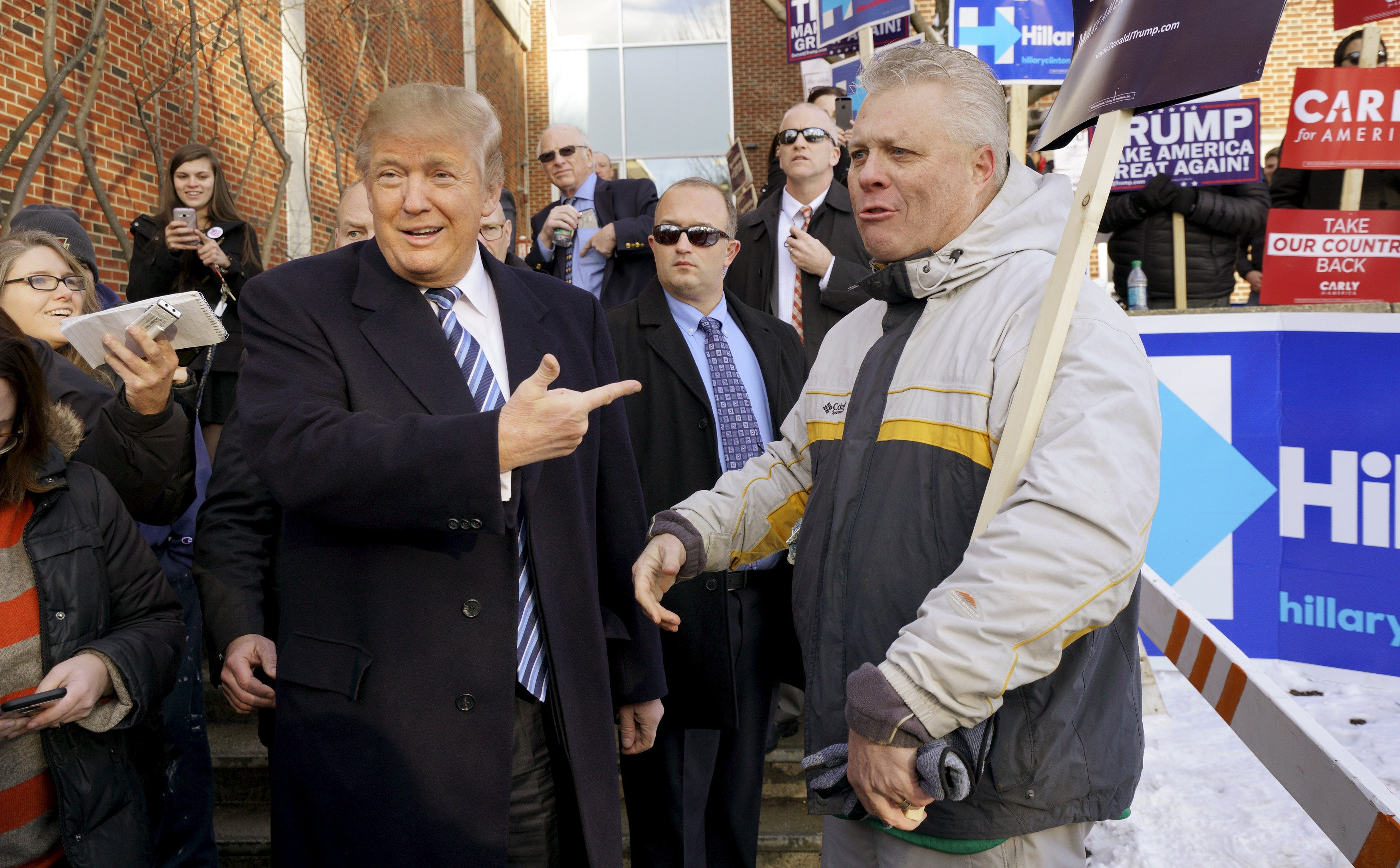 Republican presidential candidate Donald Trump points at a supporter at a polling place for the presidential primary in Manchester, New Hampshire.