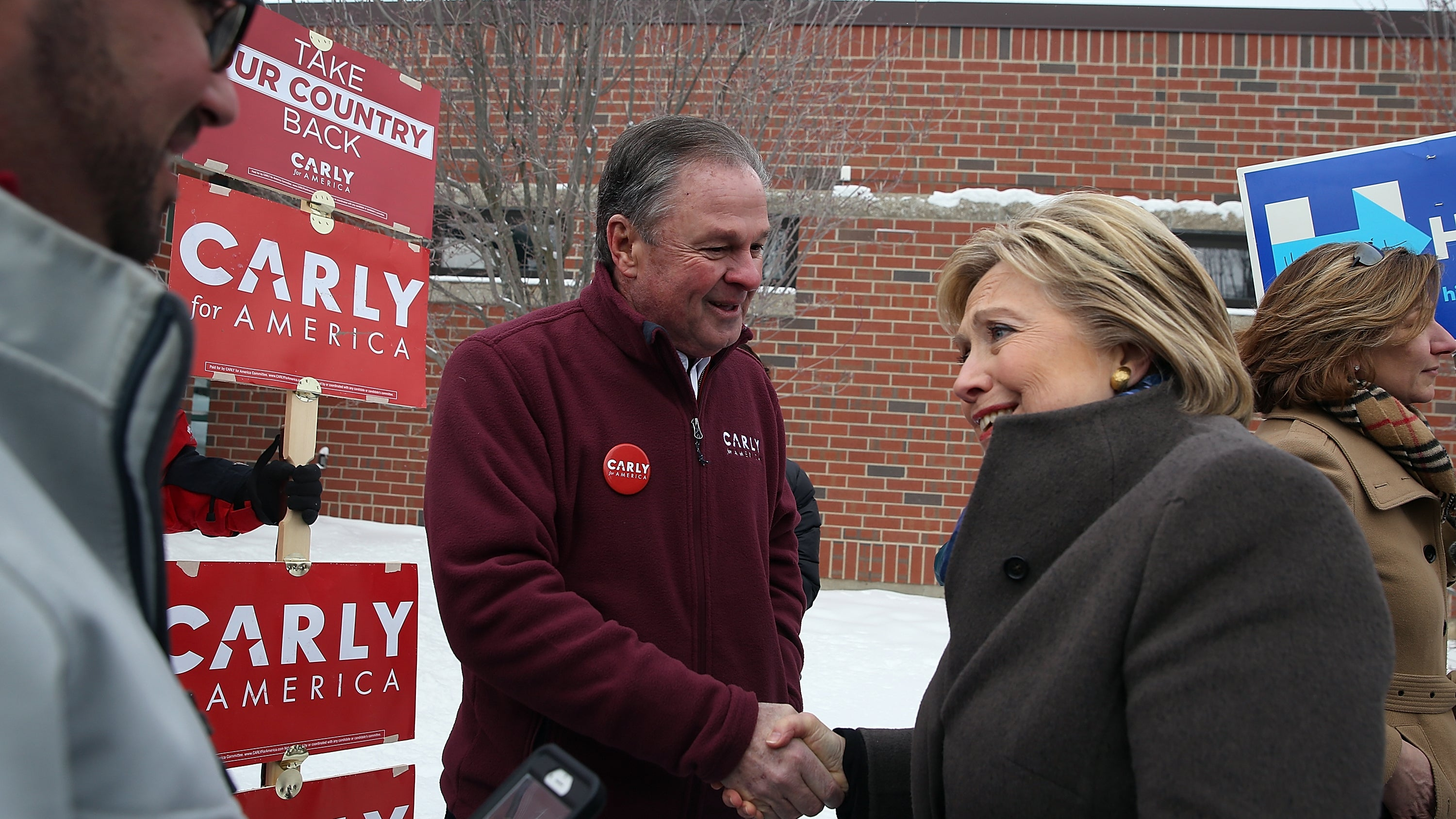 Clinton greets Frank Fiorina, husband of republican presidential candidate Carly Fiorina, outside of a polling station at Gilbert H. Hood Middle School in Derry, New Hampshire.