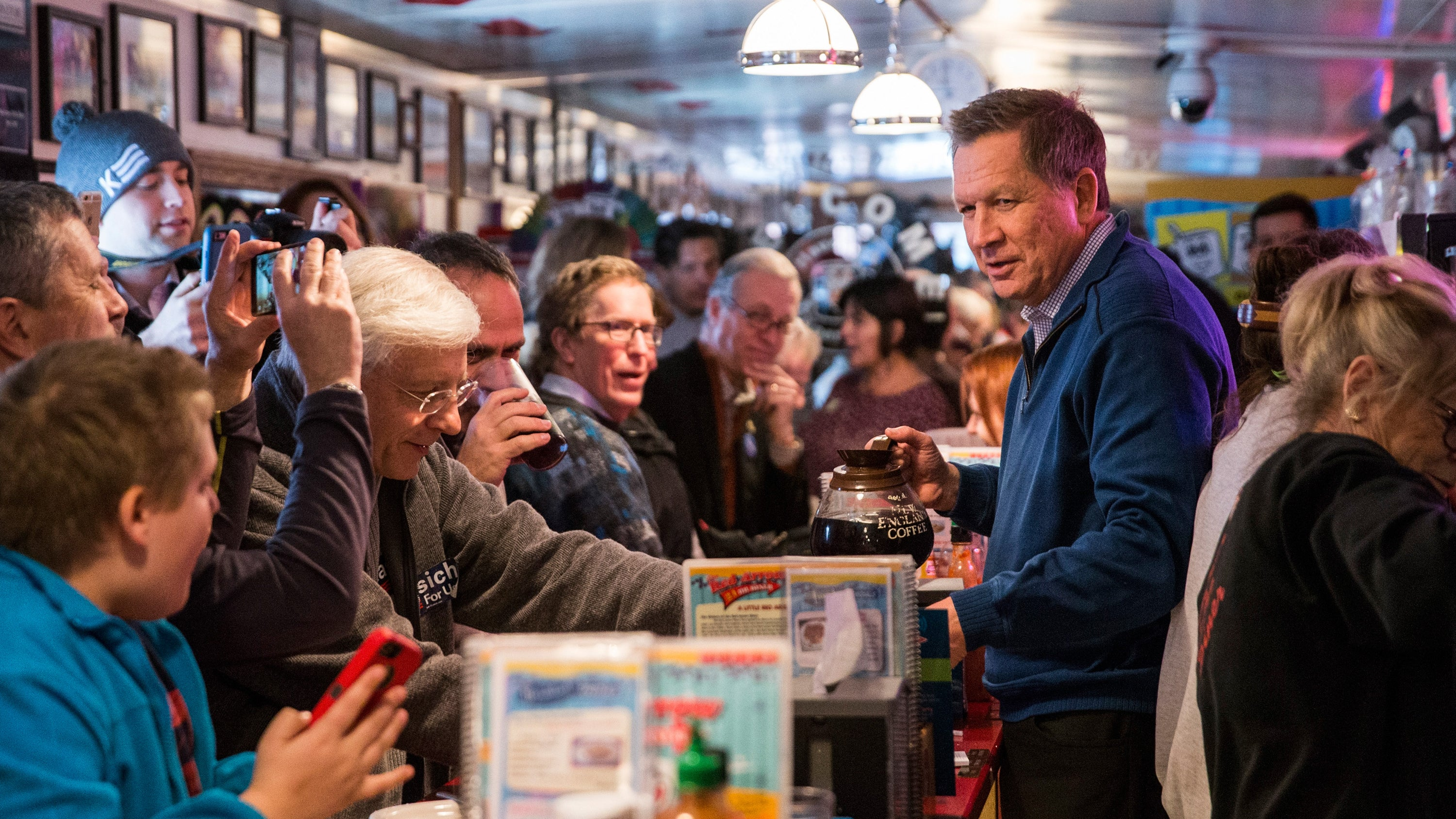 Kasich serves coffee to patrons at the Red Arrow Diner in Manchester, New Hampshire.