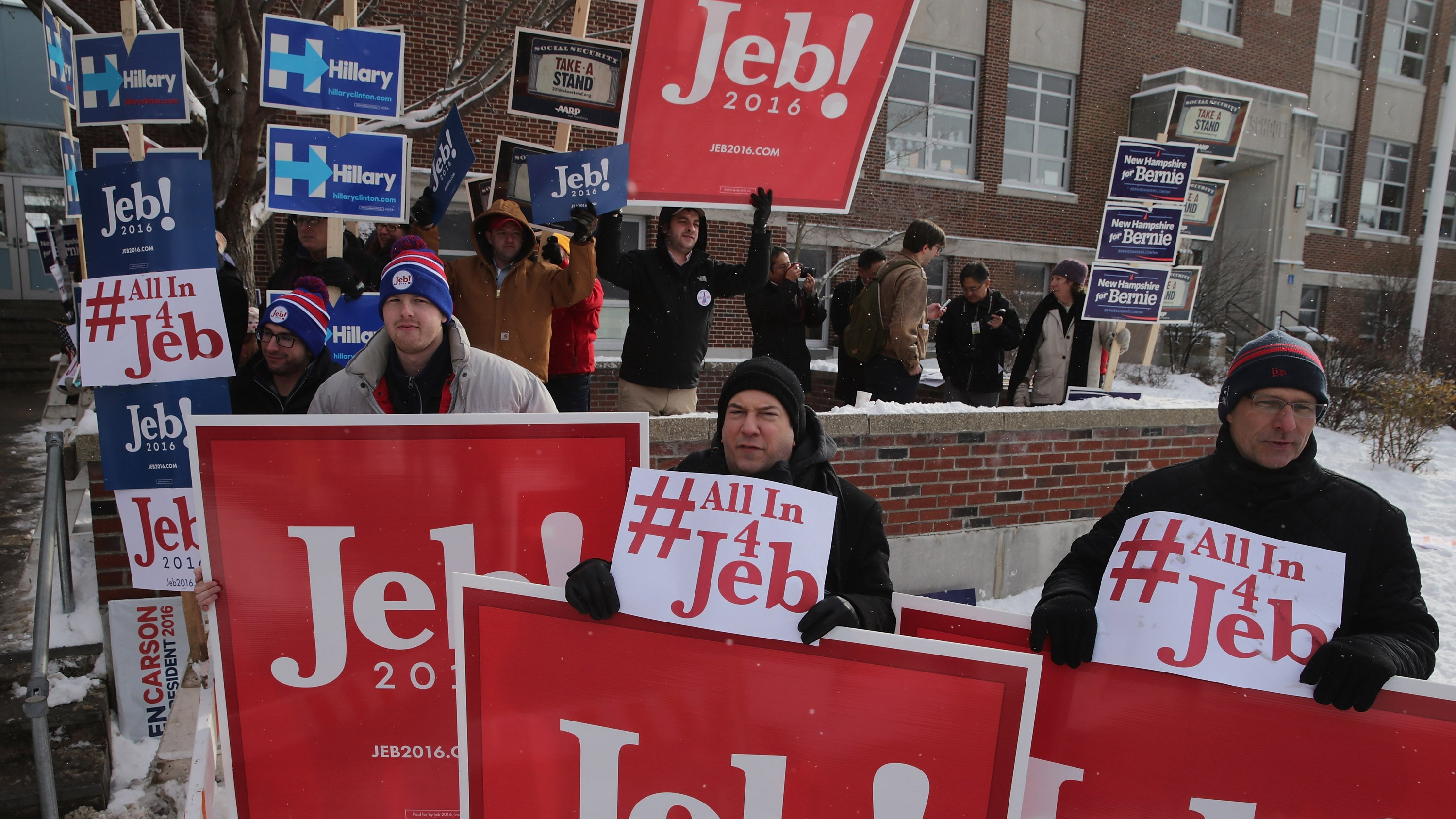 Supporters of Republican presidential candidate Jeb Bush hold campaign signs while waiting for Bush outside the polling place at Webster School on primary day in Manchester, New Hampshire.