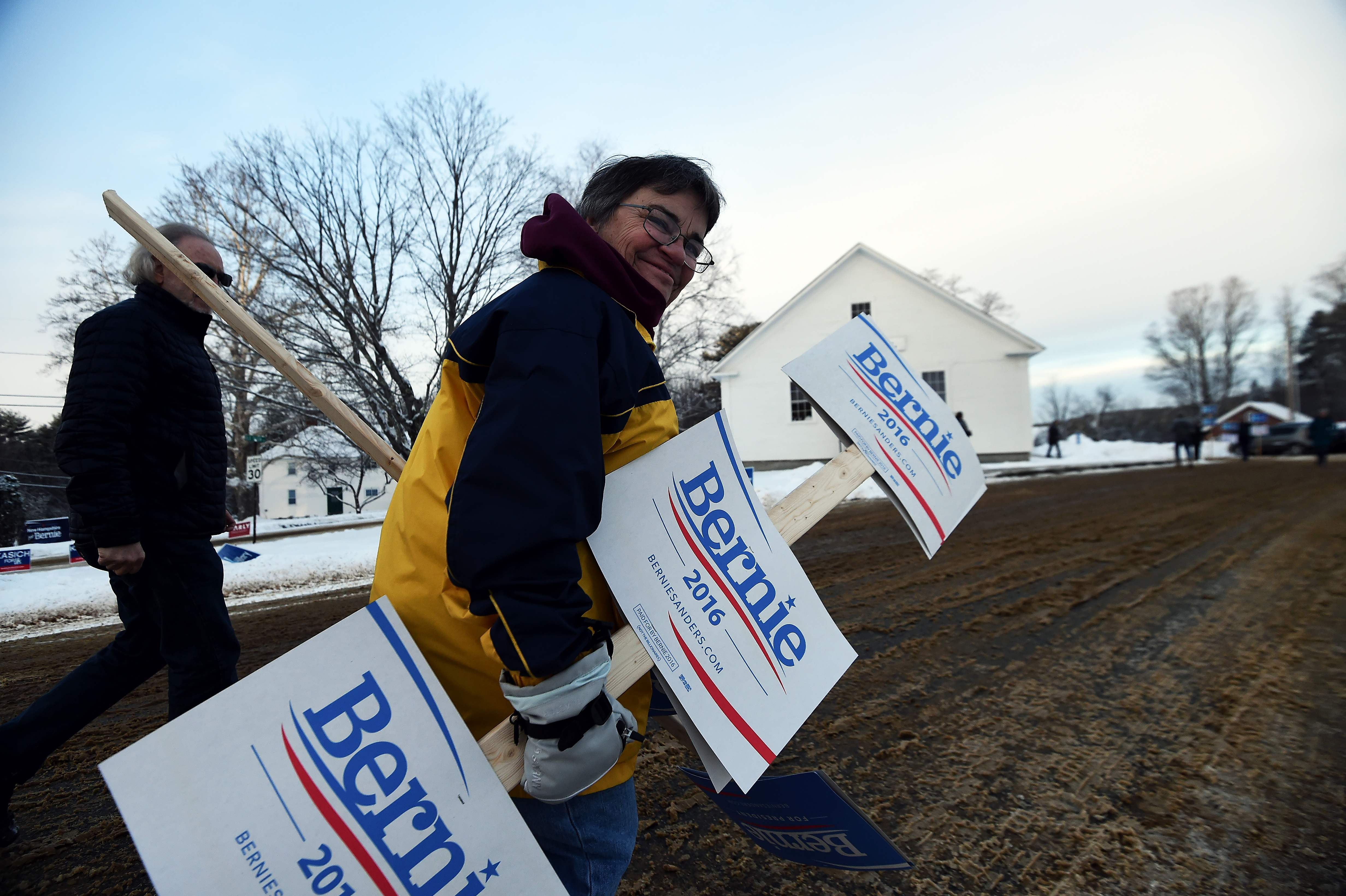 A supporter of Democratic presidential candidate Bernie Sanders arrives with campaign posters in Canterbury, New Hampshire.