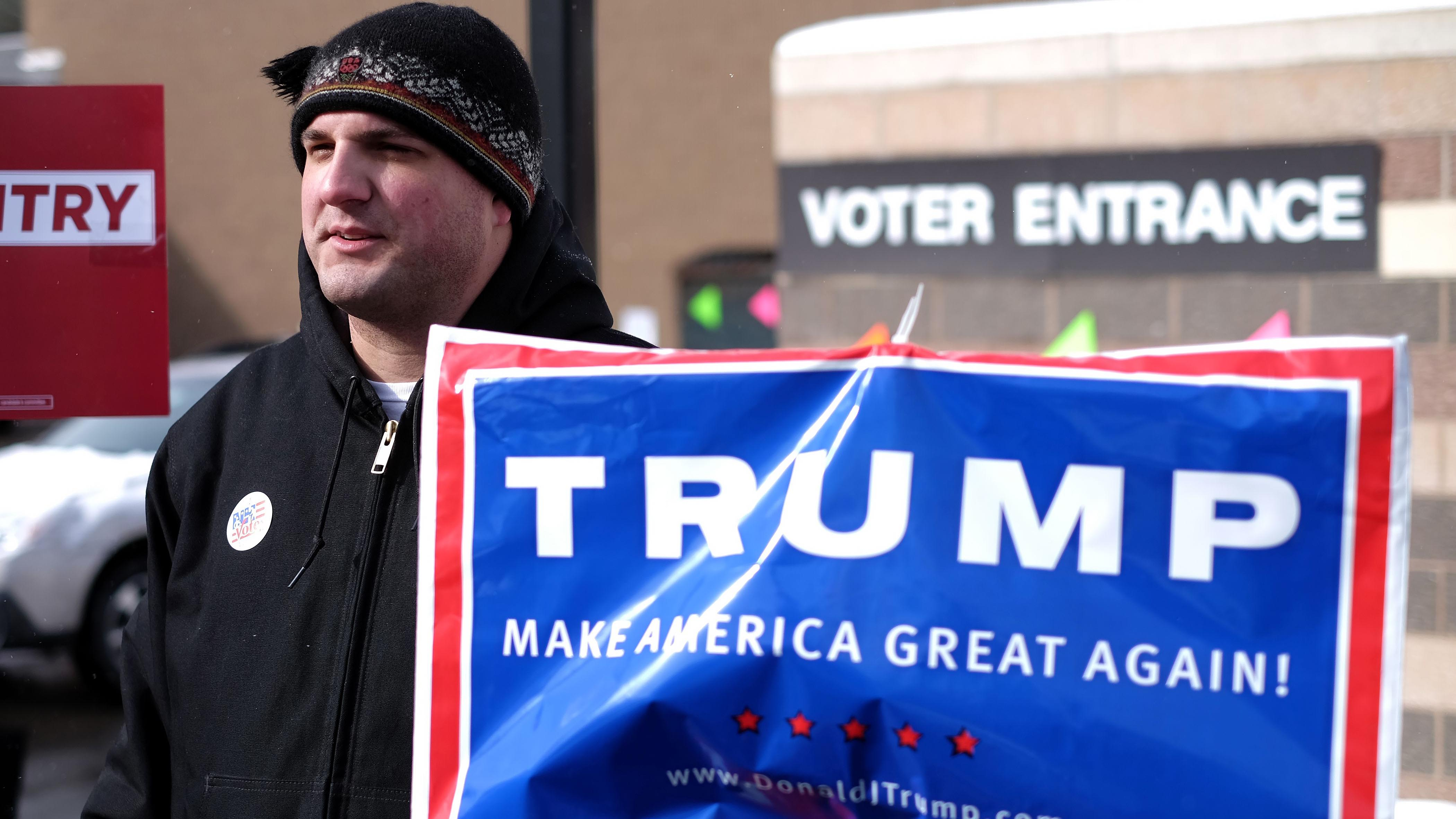 A supporter of Republican presidential candidate Donald Trump displays a campaign poster as residents vote for the first presidential primary at a school gym in Concord, New Hampshire.