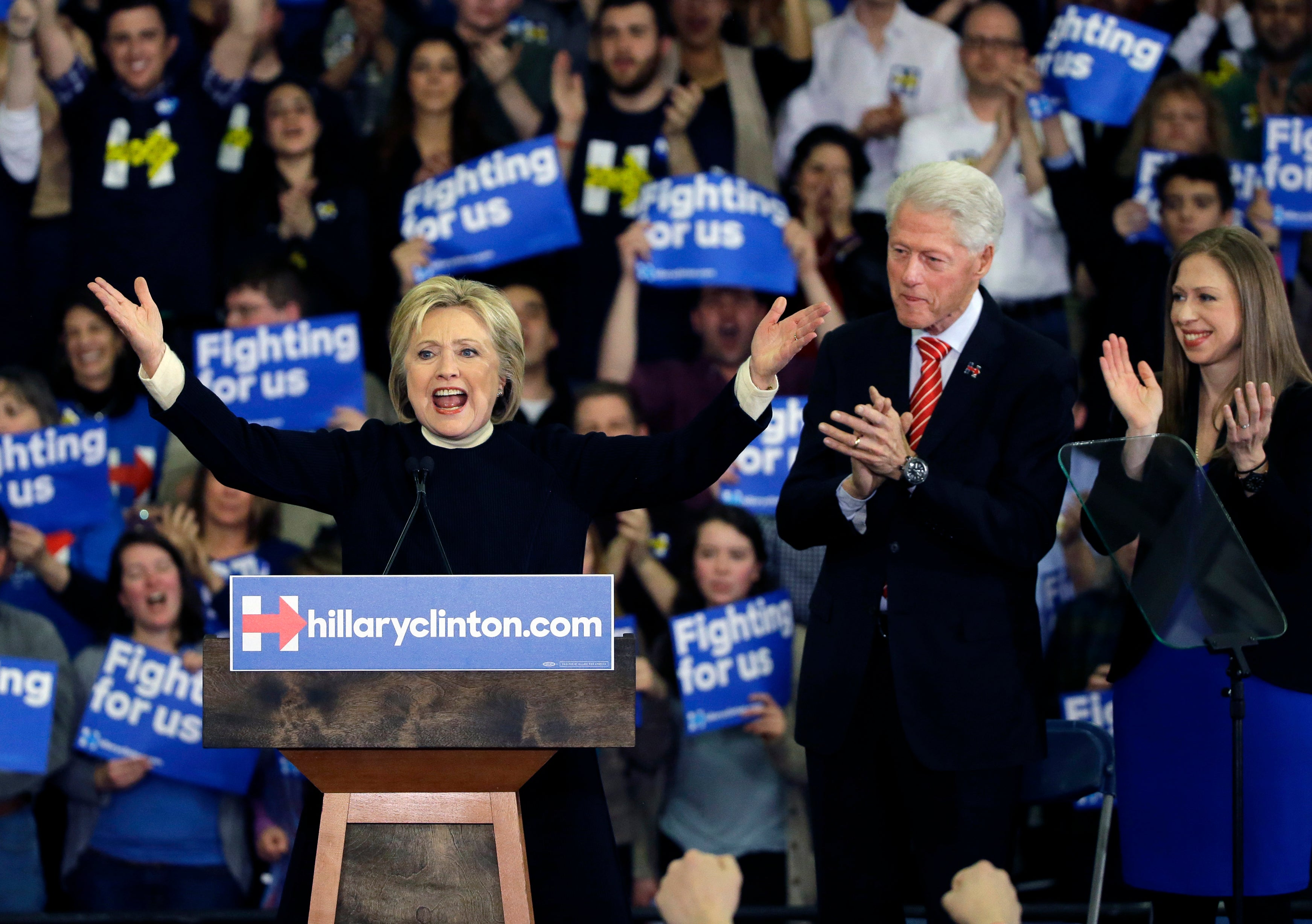 Clinton speaks as former President Bill Clinton and daughter Chelsea applaud at her New Hampshire presidential primary campaign rally.