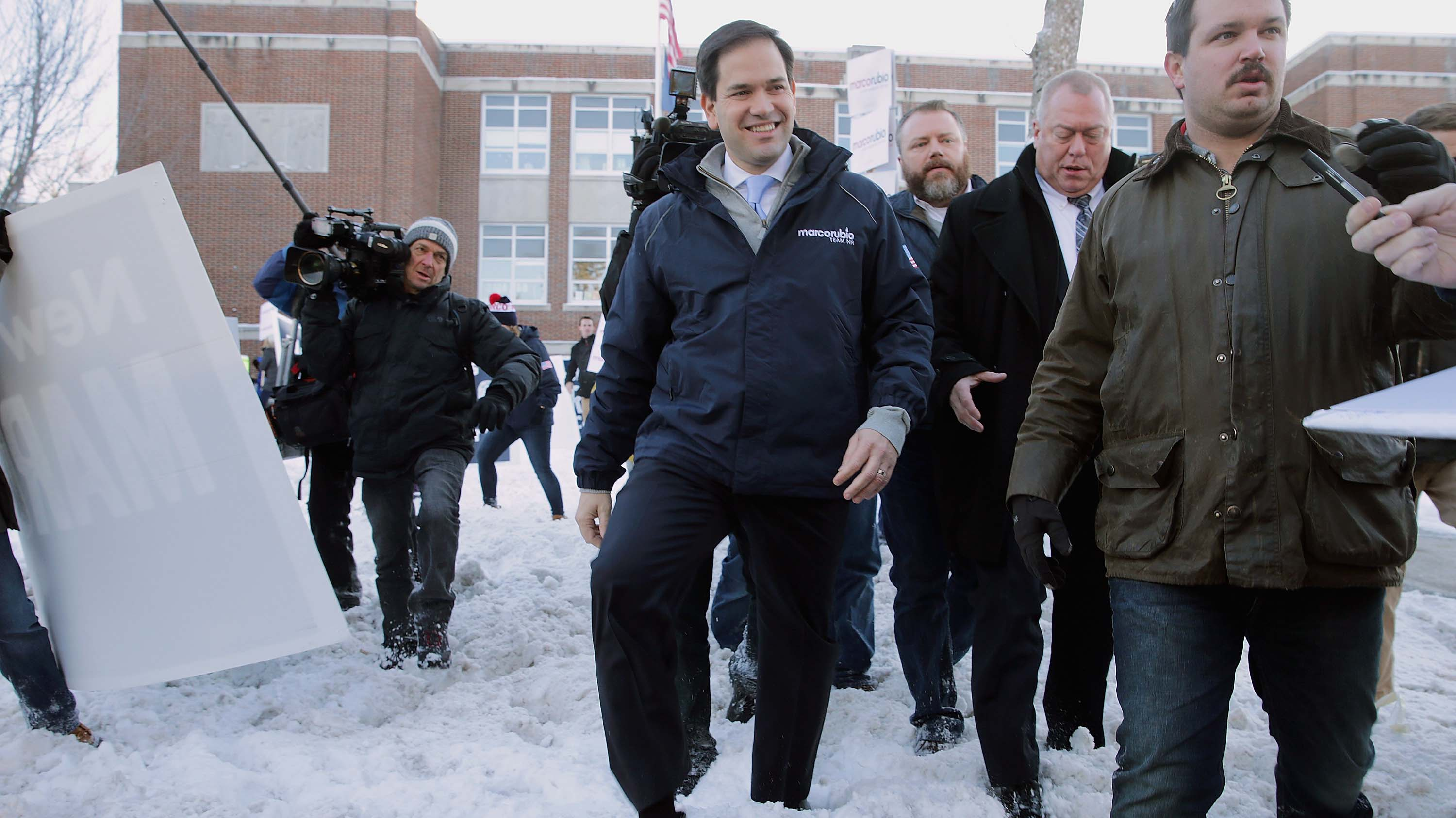Rubio walks through the snow after stopping to thank supporters outside the polling place at Webster School in Manchester, New Hampshire.