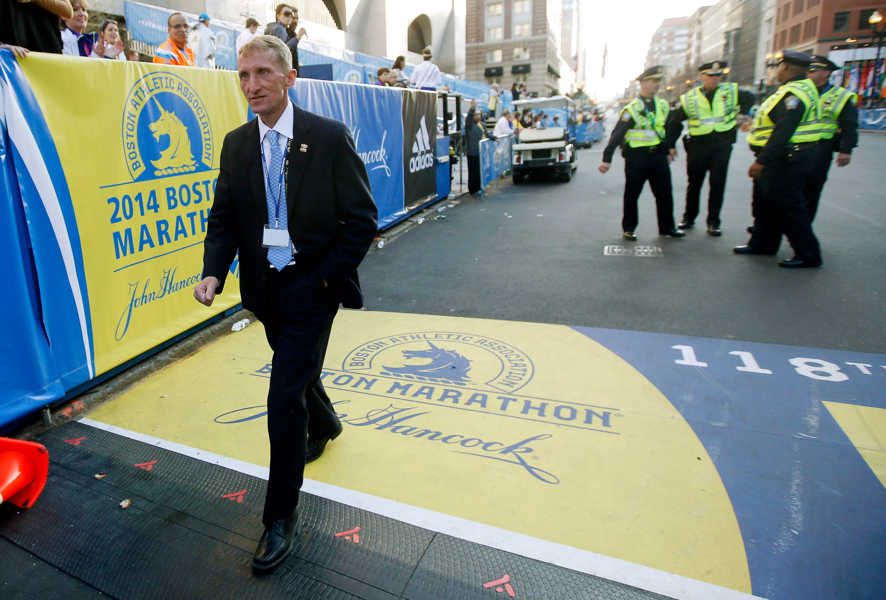 FILE - In this Monday April 21, 2014 file photo, Boston Police Commissioner William Evans walks across the finish line after the 118th Boston Marathon in Boston. The recent bombing in Brussels has heightened security concerns for this year's Boston Marathon. Evans, who is an accomplished athlete, said he will sit out the race because he says he's needed amid increased security following the attacks in Brussels. (AP Photo/Elise Amendola, File)