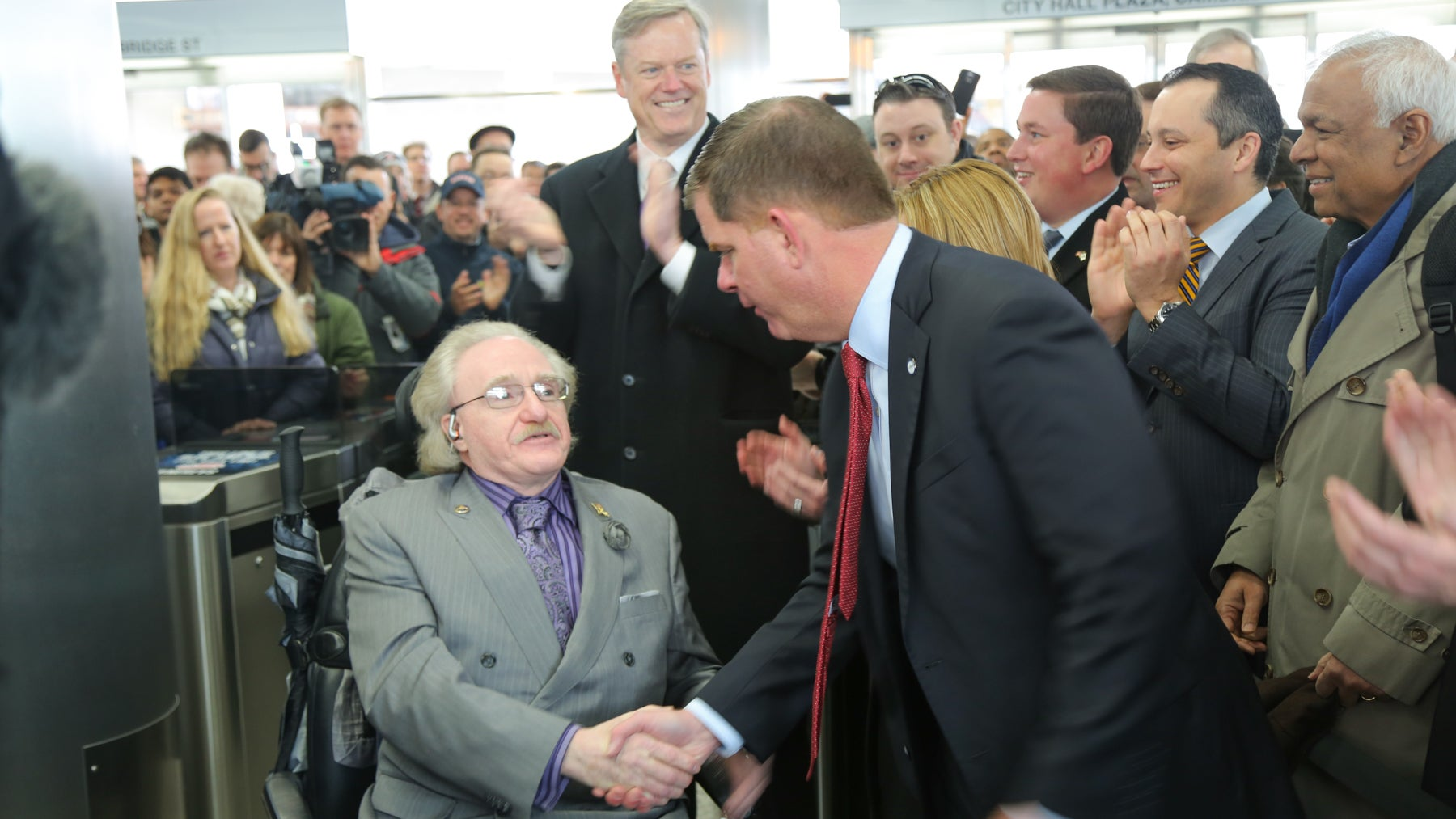 Jim White, chairman of the Access Advisory Committee to the MBTA, shakes hands with Boston Mayor Marty Walsh at the reopening of the newly accessible Government Center station. Gov. Charlie Baker was also present.