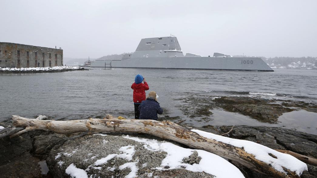 Dave Cleaveland and his son, Cody, photograph the USS Zumwalt on Monday as it passes Fort Popham at the mouth of the Kennebec River in Phippsburg, Maine.