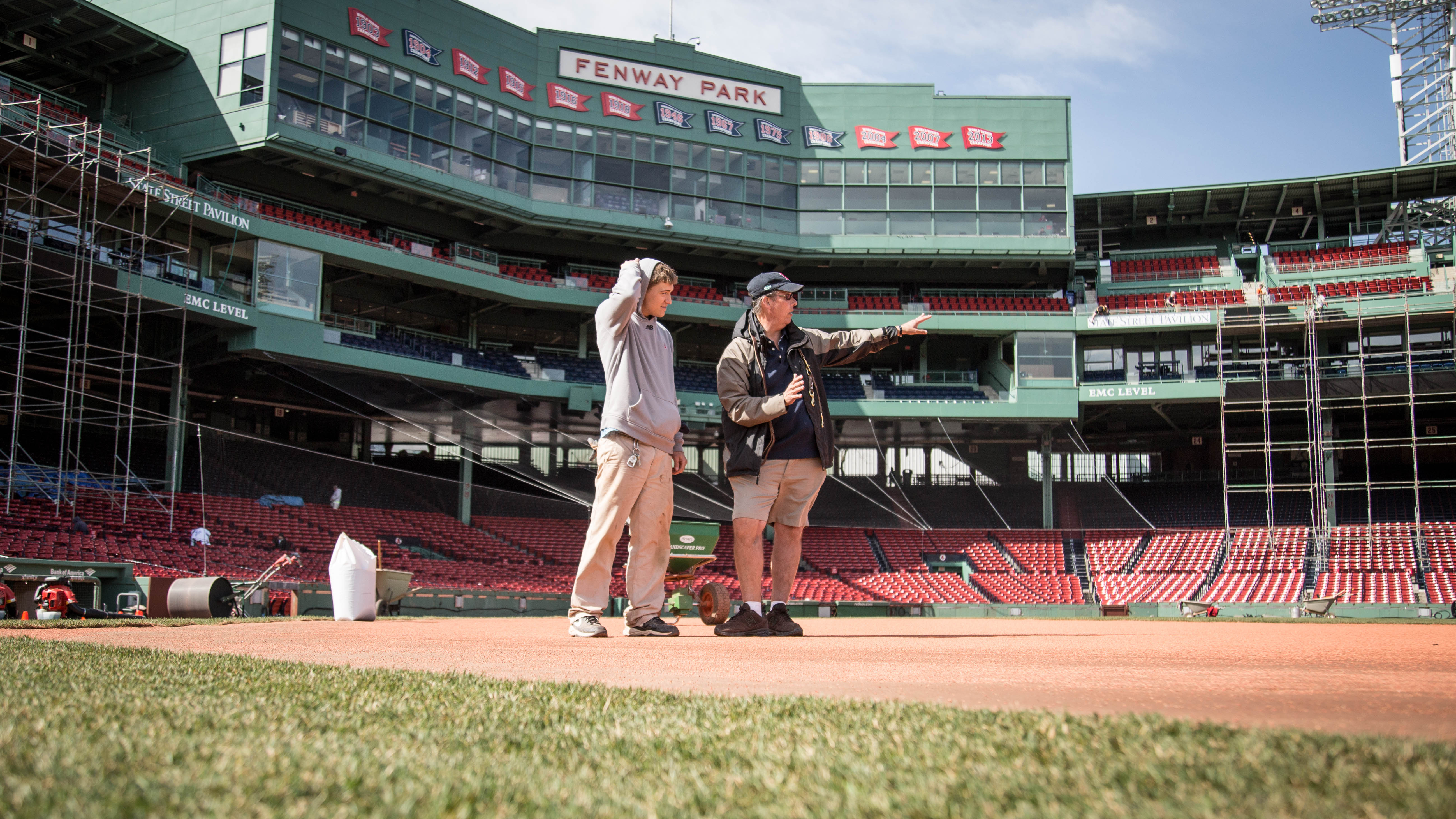 Red Sox groundskeeper Dave Mellor, right, instructs a team employee on his next move.