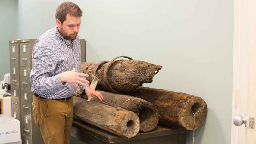 Bagley stands beside early 19th century wooden water pipes from the former sewer and water lines in the streets of downtown Boston.