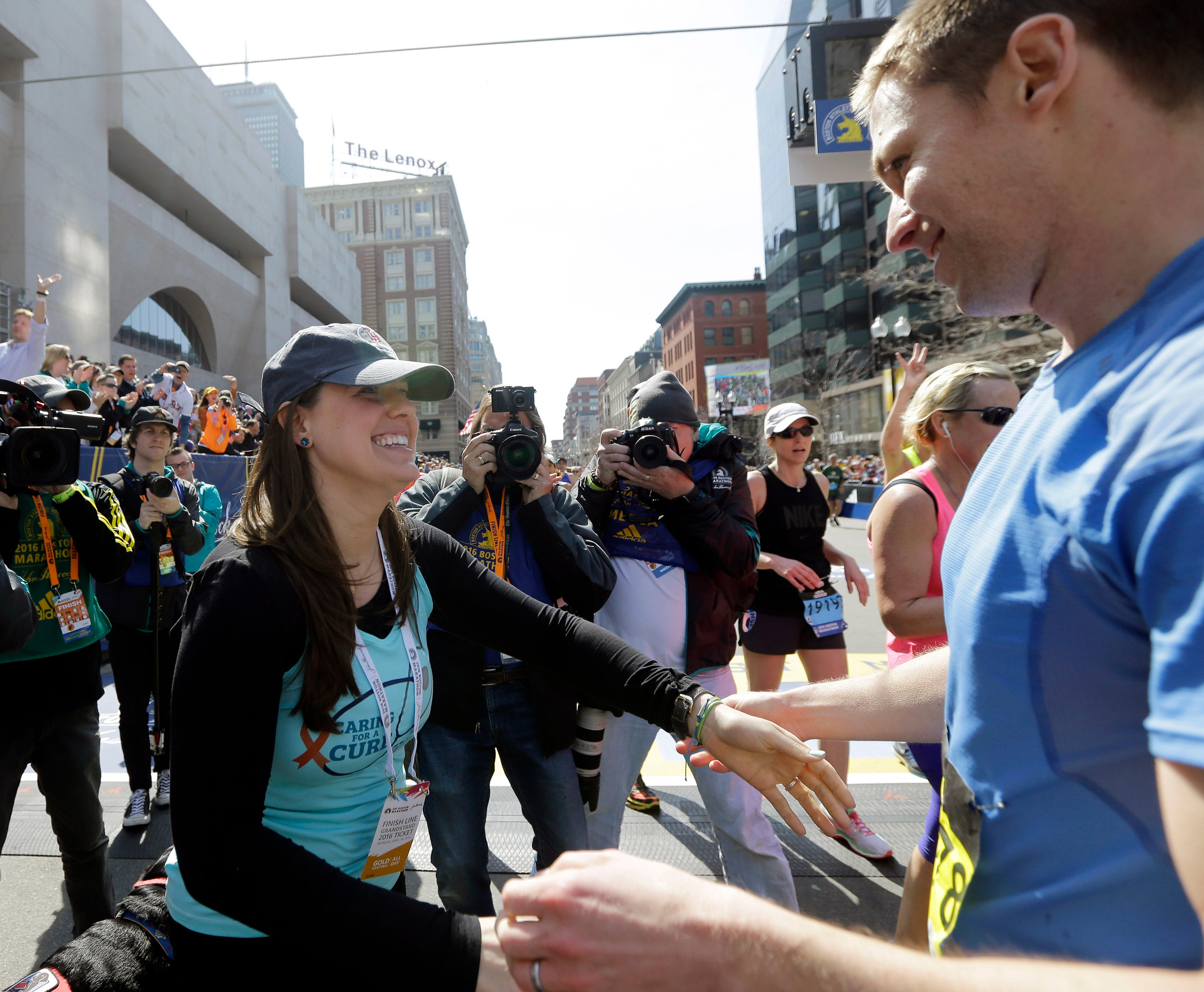Boston Marathon bombing survivor Patrick Downes, right, gets a hug from his wife Jessica after finishing the the 120th Boston Marathon on Monday, April 18, 2016, in Boston. Both lost a leg in the 2013 bombings. (AP Photo/Elise Amendola)