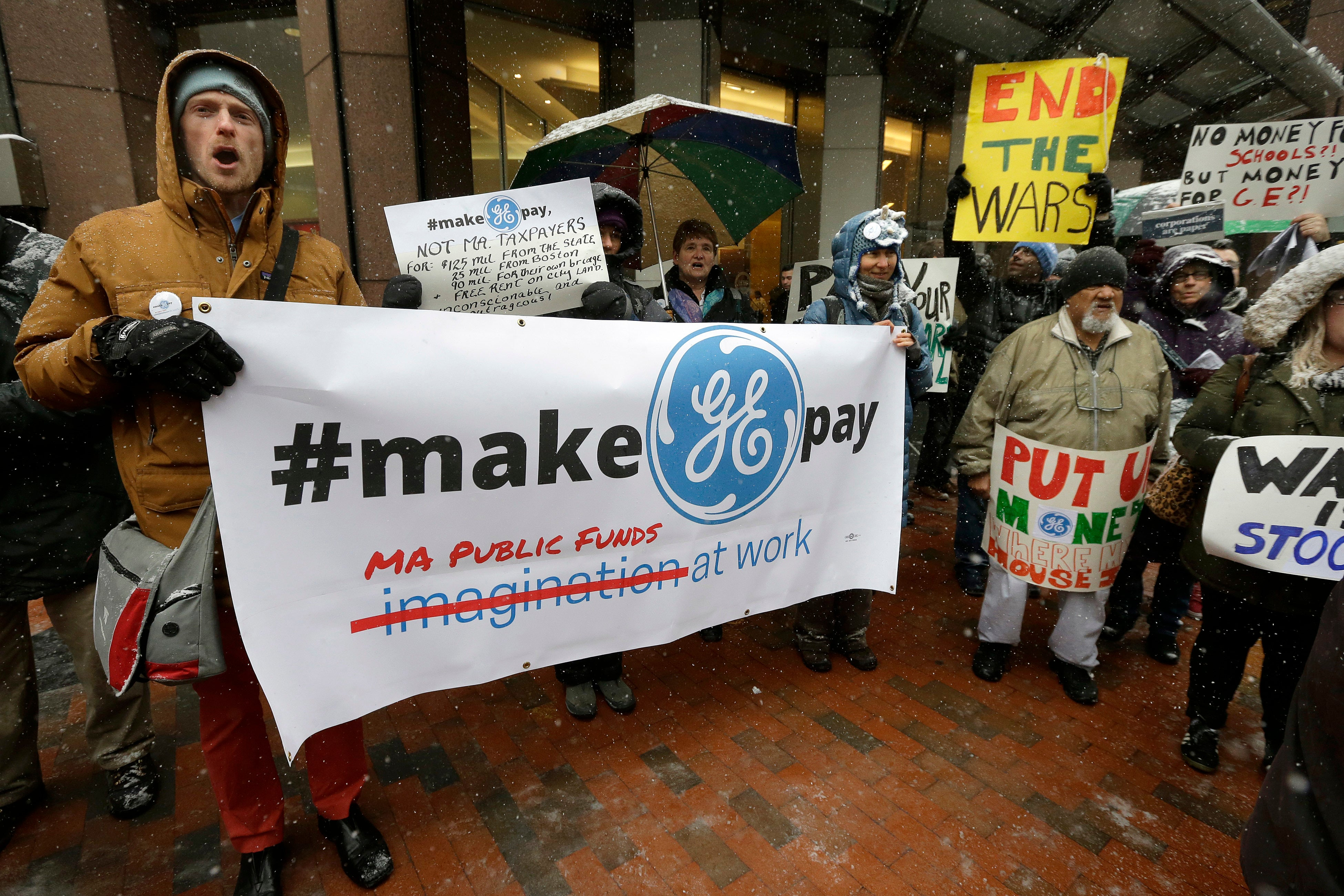 Protesters display placards outside the location of a news conference by General Electric CEO Jeff Immelt, Massachusetts Gov. Charlie Baker, and Boston Mayor Marty Walsh.
