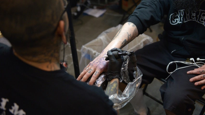 Tattoo artist Geo finds some space for a new piece on Mike Murray's already-tattooed hand.