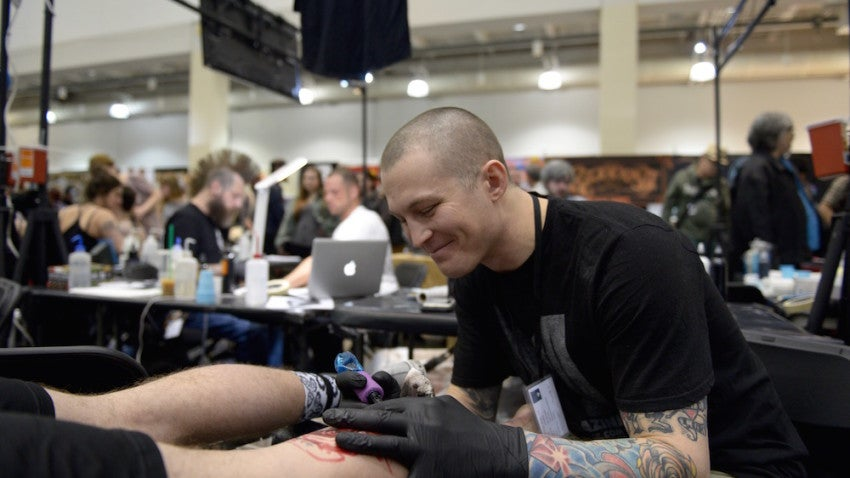 Luke Palan of Boston Tattoo Company works on a calf piece.