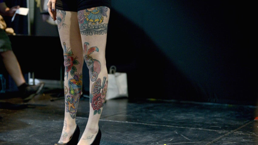 A Miss Boston Ink contestant shows off her decorated legs to the audience.