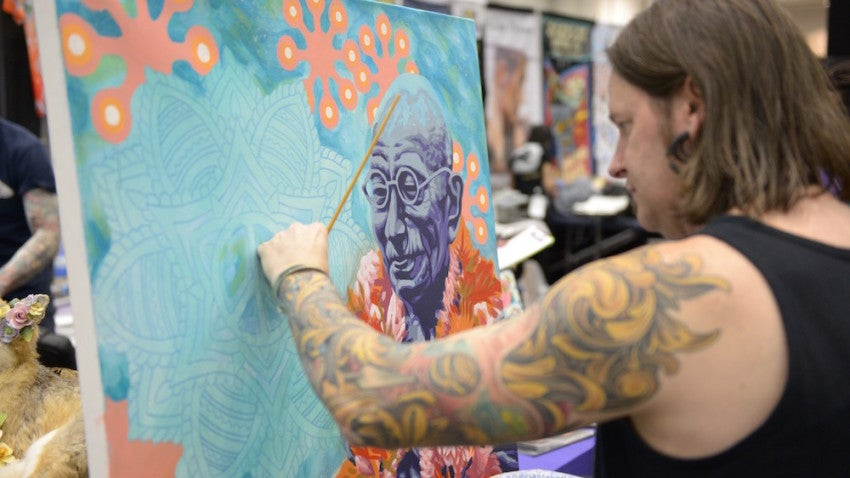 Artist Canman touches up a bright canvas with an even brighter-colored arm.