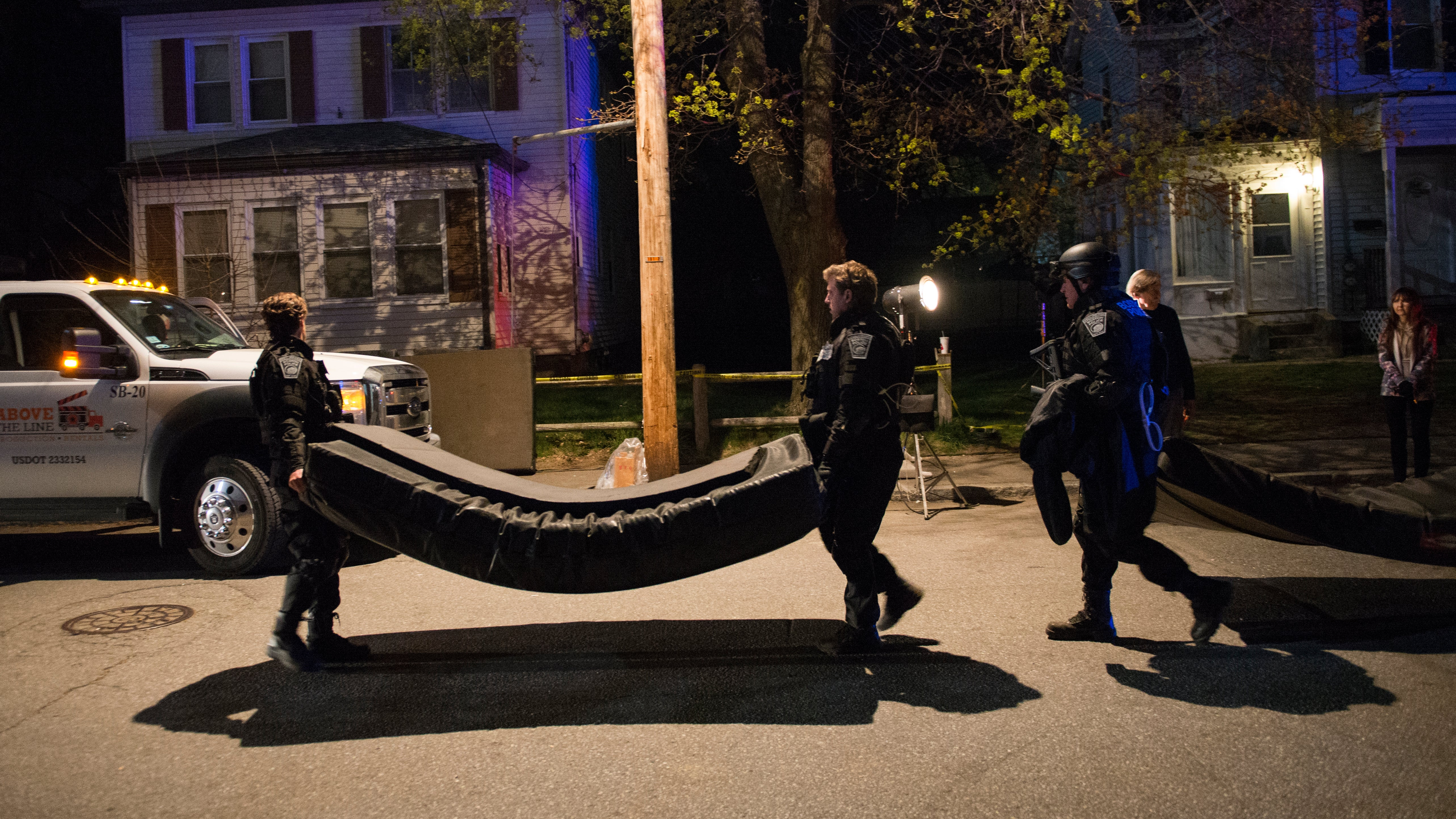 Men in police tactical gear carried what appeared to be a stunt mattress away from the film set of Patriots Day on Harrison Street in Framingham on April 22, 2016. Photo by Jim Tuttle.