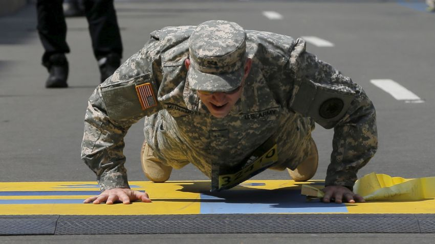 A member of the U.S. military does push-ups on the finish line during the 120th running of the Boston Marathon in Boston, Massachusetts April 18, 2016. REUTERS/Brian Snyder