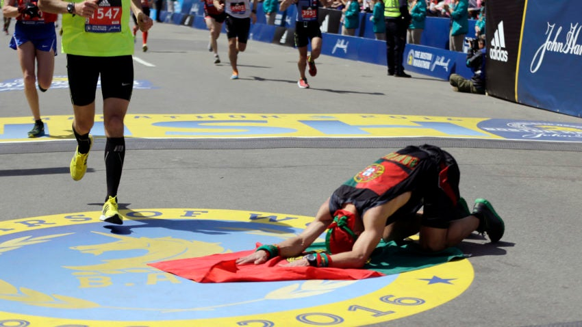 Manuel Cabral, of Canada, kneels on a flag of Portugal, after finishing the 120th Boston Marathon on Monday, April 18, 2016, in Boston. (AP Photo/Elise Amendola)