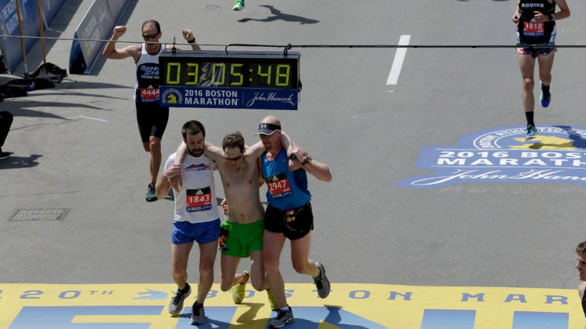 Jim Driscoll, left, of Ambler, Penn., and Mitch Kies, right, of Wimberley, Texas, help a runner across the finish line of the 120th Boston Marathon on Monday, April 18, 2016, in Boston. (AP Photo/Charles Krupa)