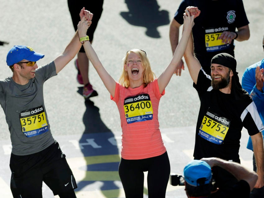 FILE - In this April 21, 2014 file photo, Timothy Haslet, left, and David Haslet, right, celebrate with their sister Adrianne Haslet-Davis at the finish line of the 118th Boston Marathon, after she completed a short distance of the course in Boston. Haslet-Davis said she is training to run the entire Boston Marathon on Monday, April 18, 2016. Haslet-Davis lost her left leg below the knee in the April 2013 bombing attacks, which killed three people and wounded more than 260 others. (AP Photo/Charles Krupa, File)