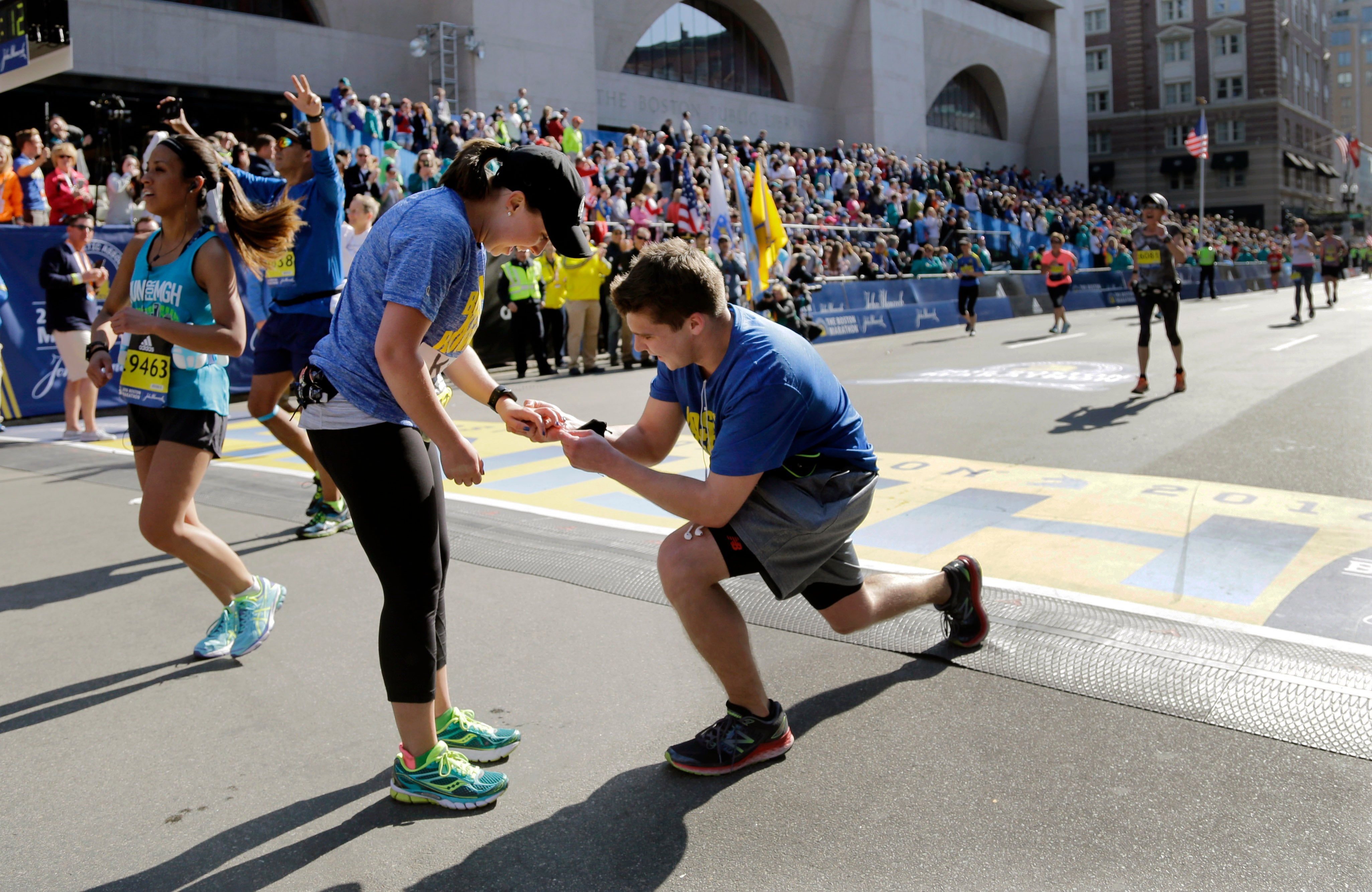 Harrison Moulton, right, slips an engagement ring onto the finger of Kellie Marshall, both of Danvers, Mass., at the finish line after they completed the 120th Boston Marathon on Monday, April 18, 2016, in Boston.