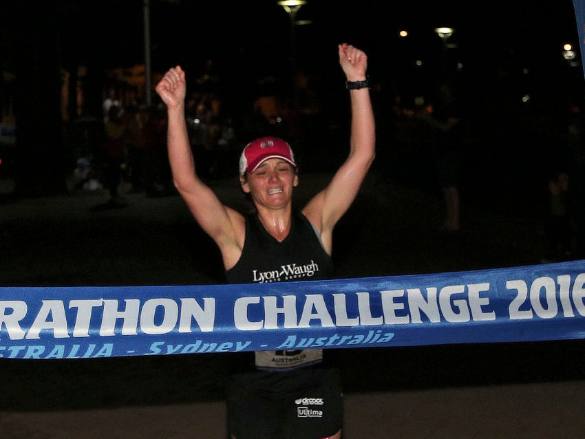 Becca Pizzi, of the United States, crosses the finish line to win the seventh and final leg of the World Marathon Challenge, Saturday, Jan. 30, 2016, in Sydney, Australia. Pizzi, from Belmont, Mass., and Daniel Cartica, of Poughkeepsie, N.Y, won the World Marathon Challenge, completing seven marathons in seven days on all seven continents. (AP Photo/Rob Griffith)