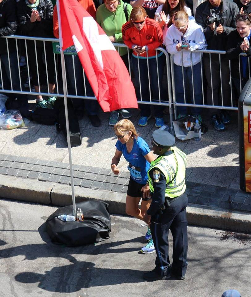 A Boston police officer helps a marathon runner steps from the finish line on Boylston Street.