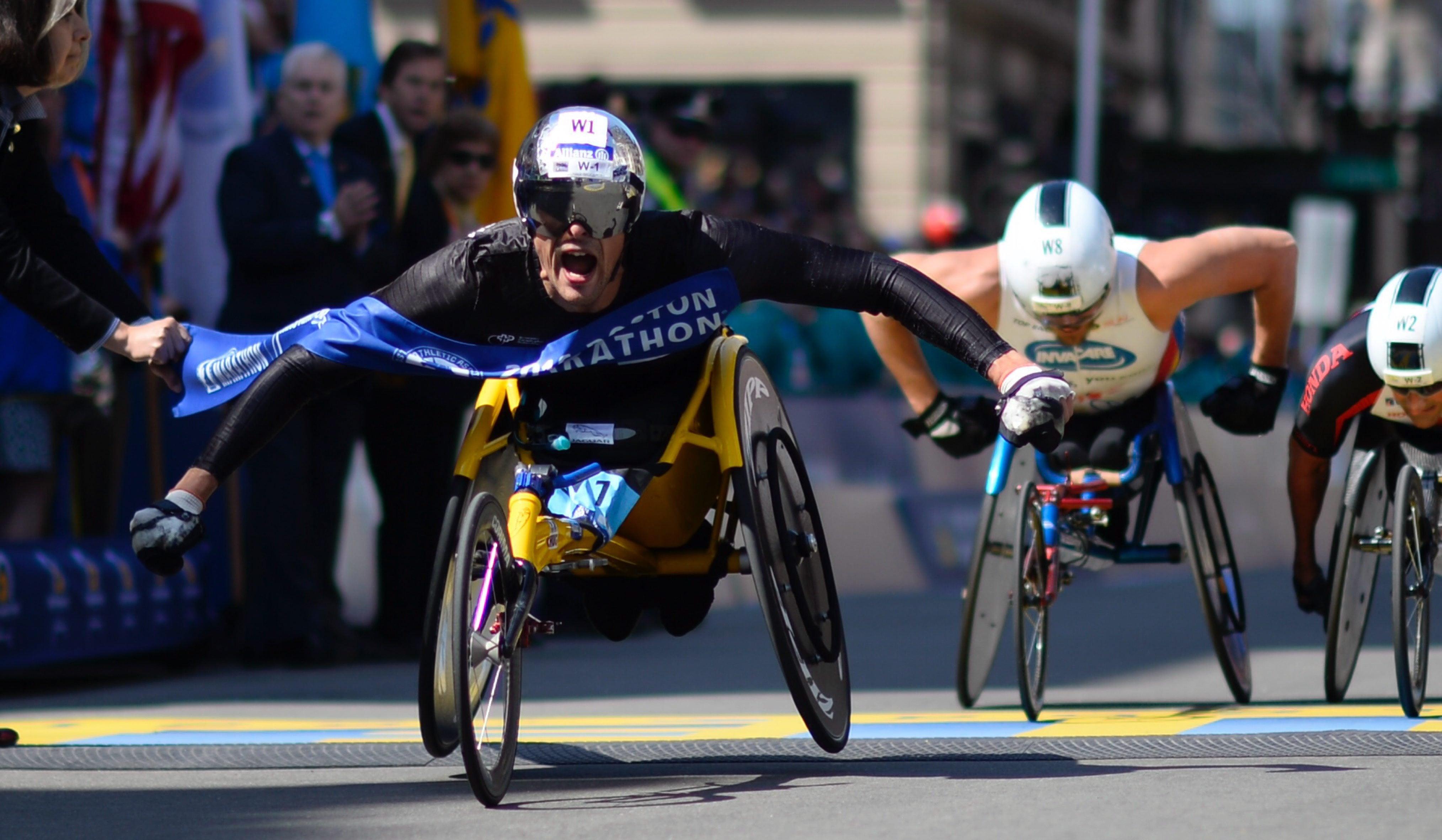epa05265682 Marcel Hug of Switzerland (L) crosses the finish line to win the Men's Wheelchair division of the 120th Boston Marathon in Boston, Massachusetts, USA, 18 April 2016. EPA/CJ GUNTHER