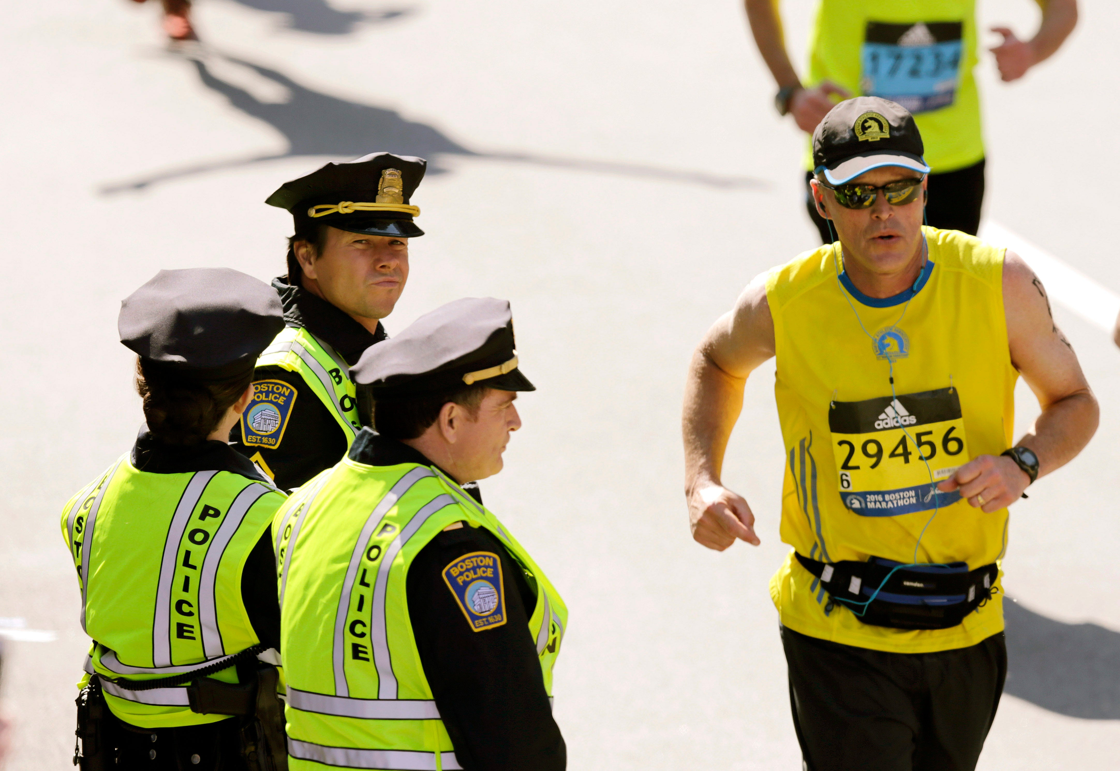 """Actor Mark Wahlberg, center left, dressed as a Boston Police officer, watches runners cross the finish line as he films a scene for his upcoming """"Patriot's Day"""" movie at the 120th Boston Marathon on Monday, April 18, 2016, in Boston. (AP Photo/Charles Krupa)"""