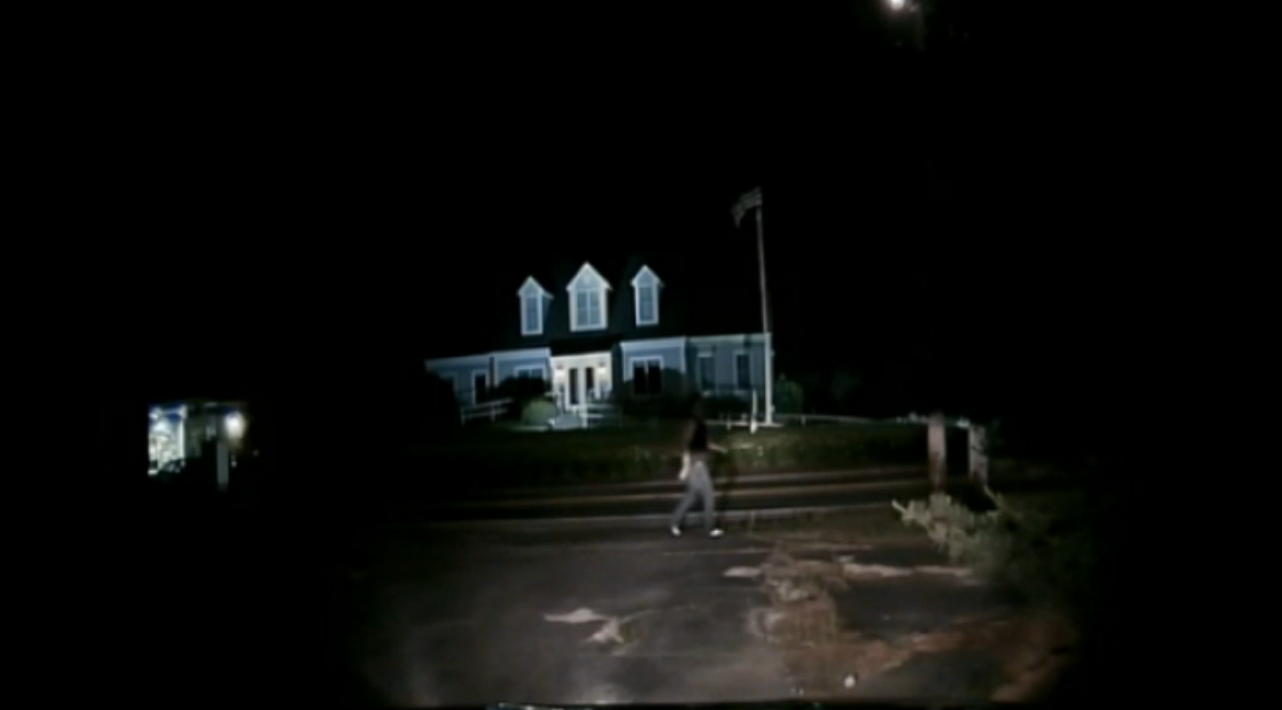 A screenshot of video captured by a Wayland police officer's cruiser dash camera. In it, a home invasion suspect walks down the street.