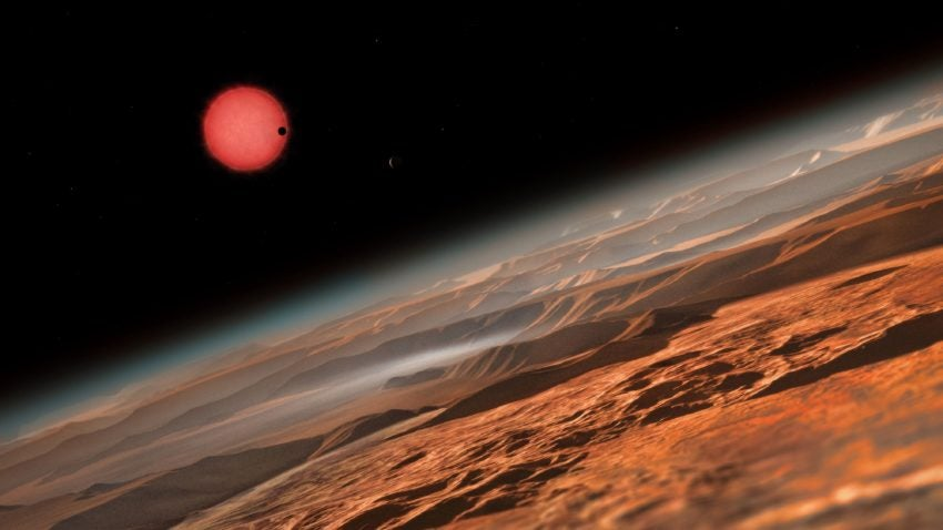 """TO GO WITH AFP STORY BY LAURENCE COUSTAL An artists impression released by the the European Southern Observatory (ESO) on May 2, 2016 shows an imagined view from close to one of the three planets orbiting an ultracool dwarf star just 40 light-years from Earth that were discovered using the TRAPPIST (""""TRAnsiting Planets and PlanetesImals Small Telescope"""") telescope at ESOs La Silla Observatory in Chile. These worlds have sizes and temperatures similar to those of Venus and Earth and are the best targets found so far for the search for life outside the Solar System. They are the first planets ever discovered around such a tiny and dim star. In this view one of the inner planets is seen in transit across the disc of its tiny and dim parent star. / AFP PHOTO / European Southern Observatory / - / RESTRICTED TO EDITORIAL USE - MANDATORY CREDIT """"AFP PHOTO / ESO """" - NO MARKETING NO ADVERTISING CAMPAIGNS - DISTRIBUTED AS A SERVICE TO CLIENTS -/AFP/Getty Images"""