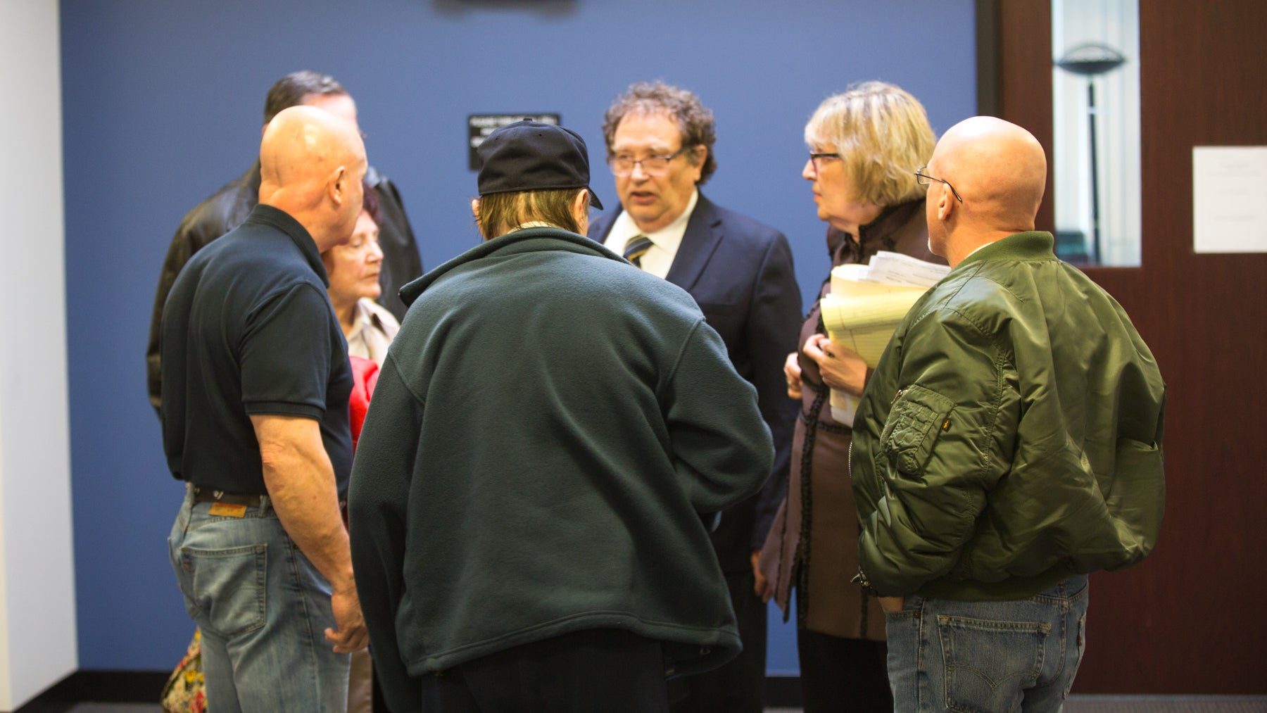 Attorneys for Jay Procopio (right, green jacket) meet with his family after a hearing in Middlesex Superior Court. From back, in suit, attorneys Robert Bloomenthal and Sandra Bloomenthal, Jay Procopio, Procopio's father Joseph Procopio, an unidentified man, Procopio's stepfather, and Procopio's mother, Marie.