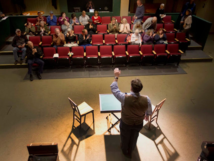 In this photo taken Wednesday, May 4, 2016, magician Andrew Pinard waves to his crowd after his performance at the Hatbox Theater in Concord, N.H. The theater took over the location of a closed clothing store at the Steeplegate Mall. Malls are attempting to reinvent themselves to stem the losses that have resulted from online shopping. (AP Photo/Jim Cole)