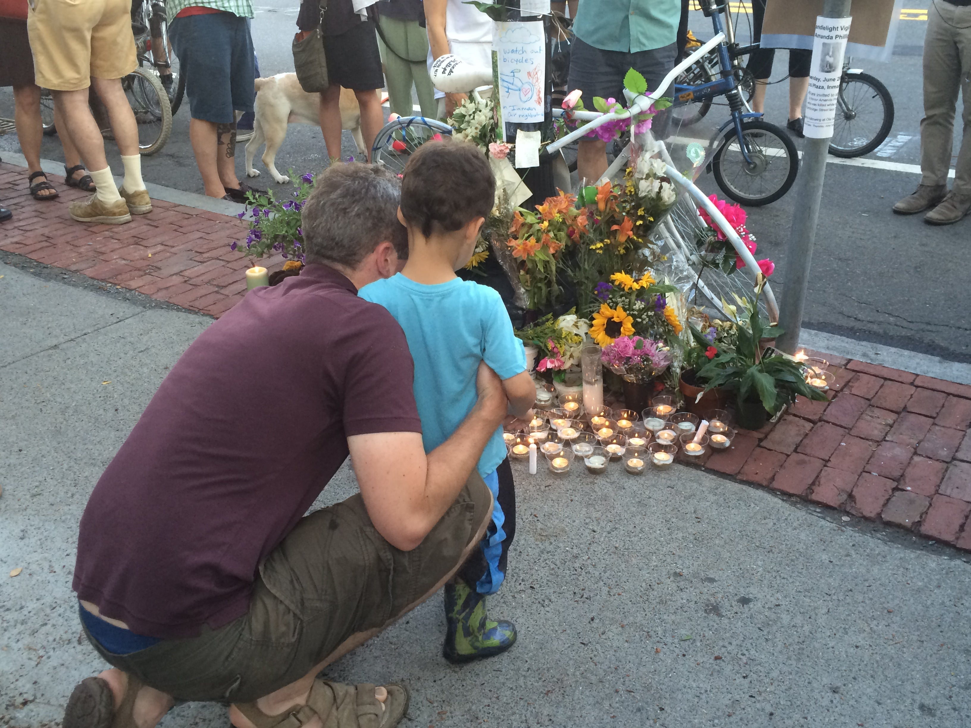 Mourners place a candle in front of the vigil for Amanda Phillips.