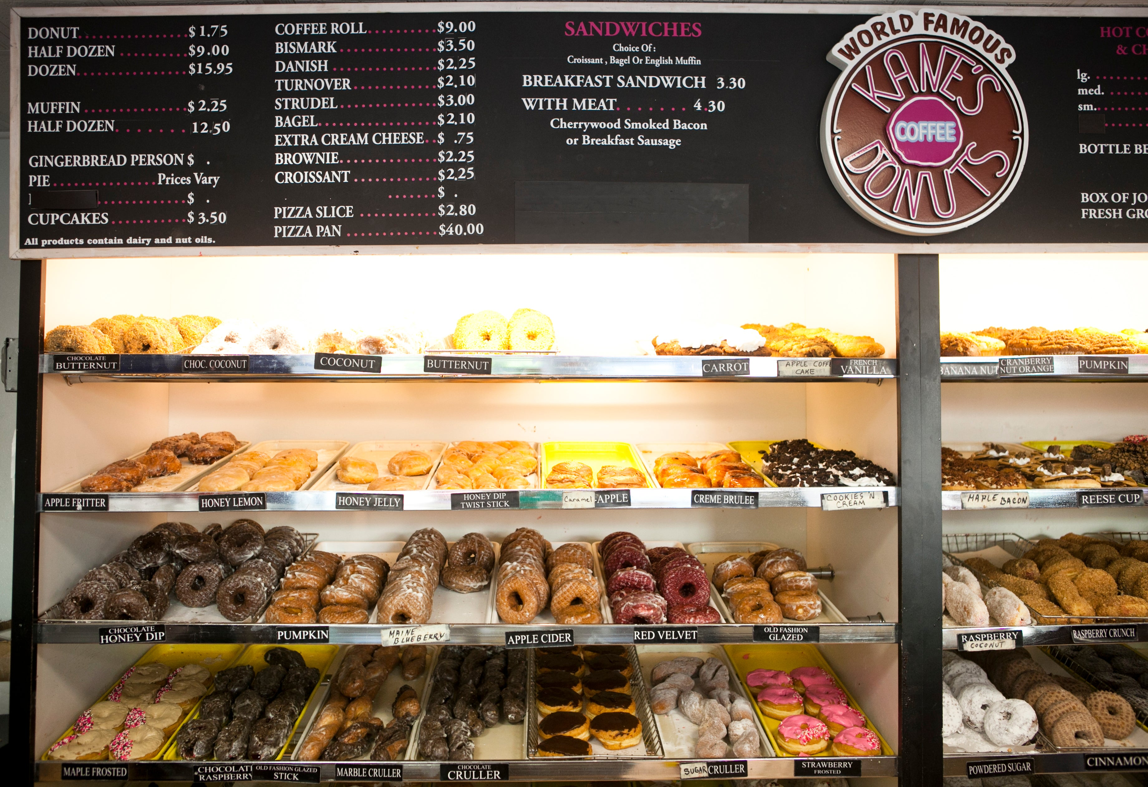 SAUGUS, MA - 09/09/14: Fresh donuts of numerous varieties lines the shelves of Kane's Donuts in Saugus Tuesday morning. Kane's is a 60-year-old institution, and Paul and Maria Delios have been making donuts since they were little kids. They still use their father's recipe and typically make several thousand donuts each day. 03kanes(2)/Business (Juliette Lynch for The Boston Globe)
