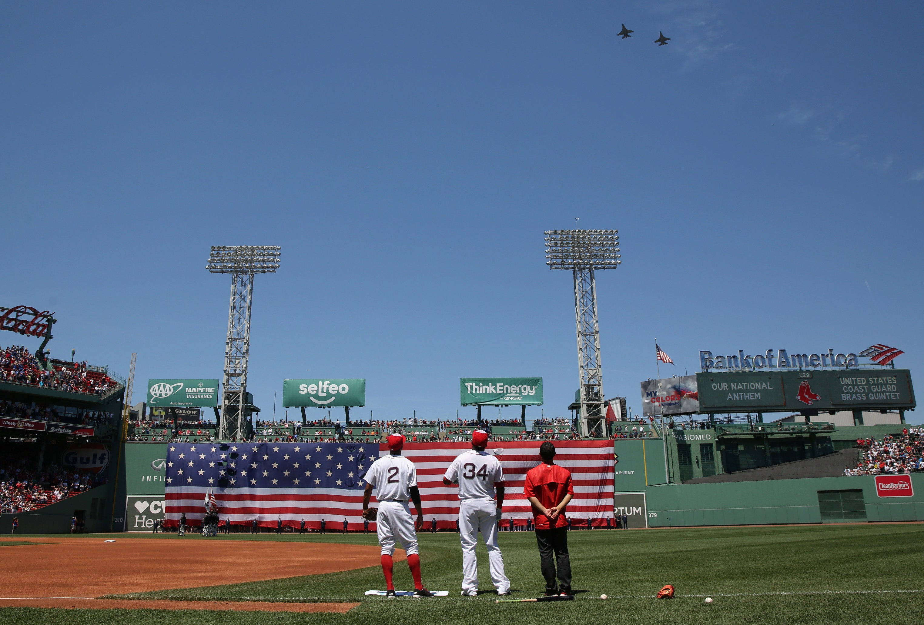 Two jets perform a flyover as a large American flag drapes over the Green Monster as part of 4th of July at Fenway Park.