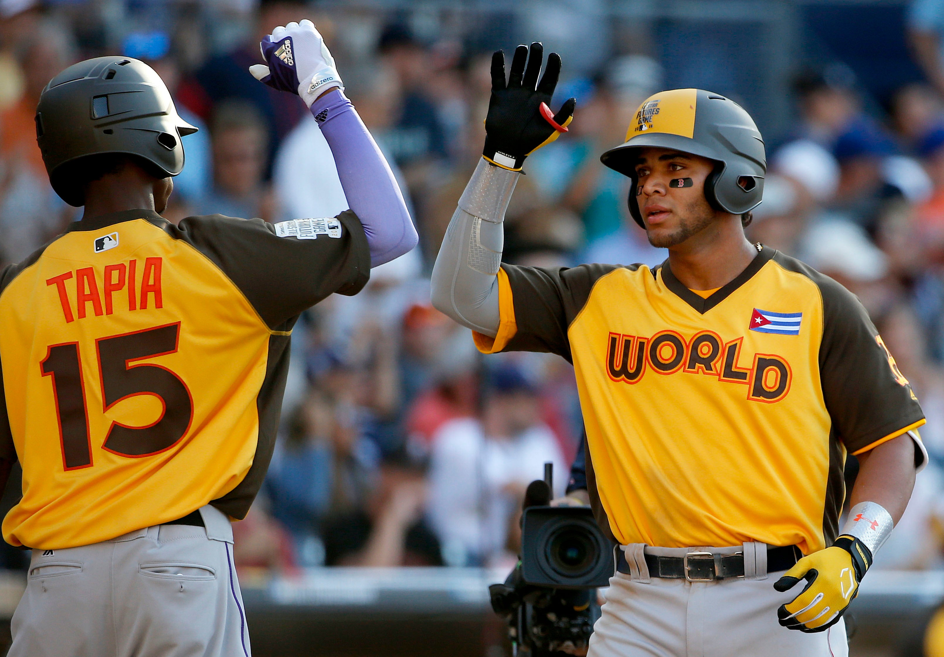 World Team's Yoan Moncada, of the Boston Red Sox, greets teammate Raimel Tapia, of the Colorado Rockies (15), after hitting a two-run home run against the U.S. Team during the eighth inning of the All-Star Futures baseball game, Sunday, July 10, 2016, in San Diego. (AP Photo/Lenny Ignelzi)
