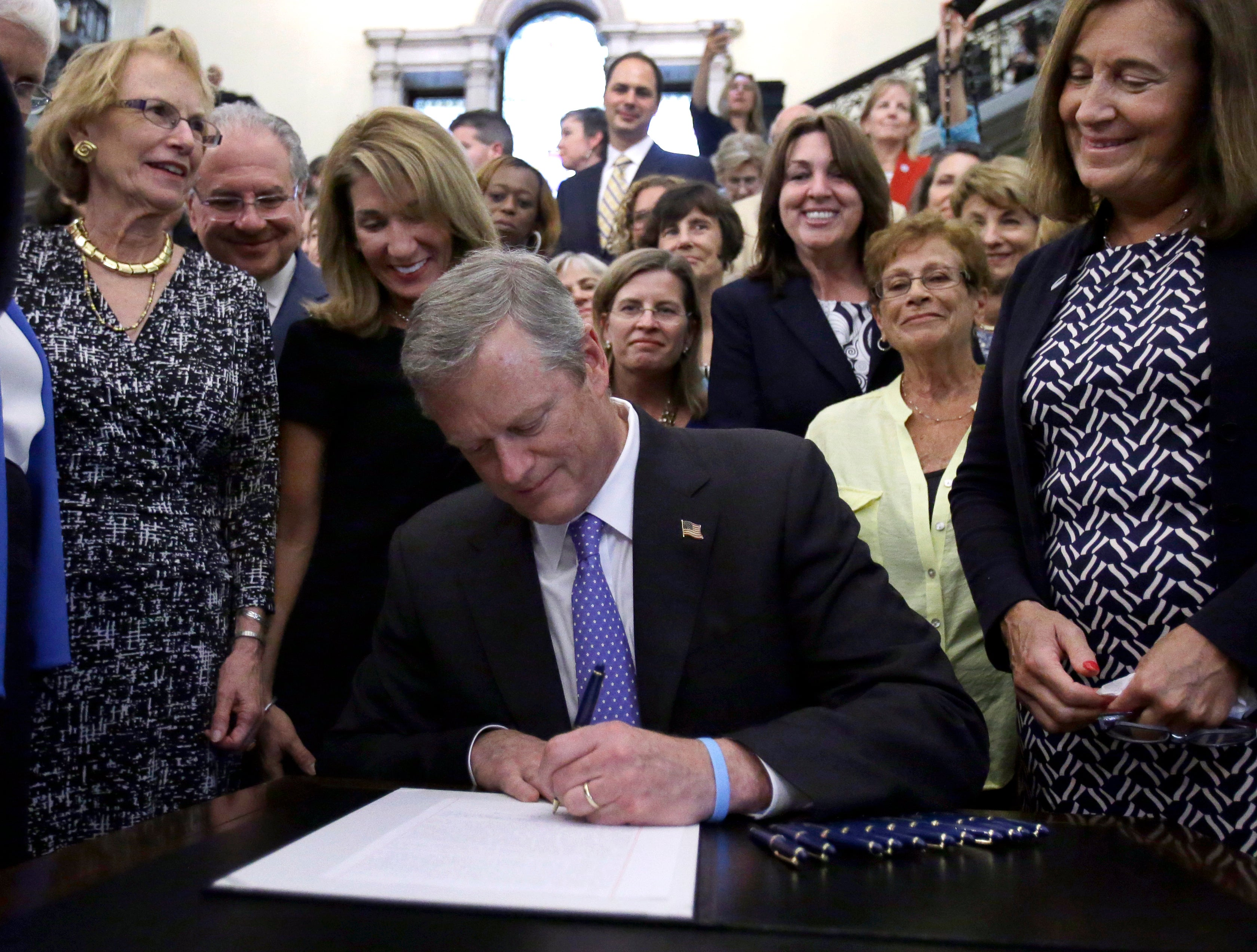Supporters watch as Massachusetts Gov. Charlie Baker signs a bill into law at the Statehouse, Monday, Aug. 1, 2016, in Boston. The law requires comparable pay for men and women in Massachusetts. (AP Photo/Elise Amendola)
