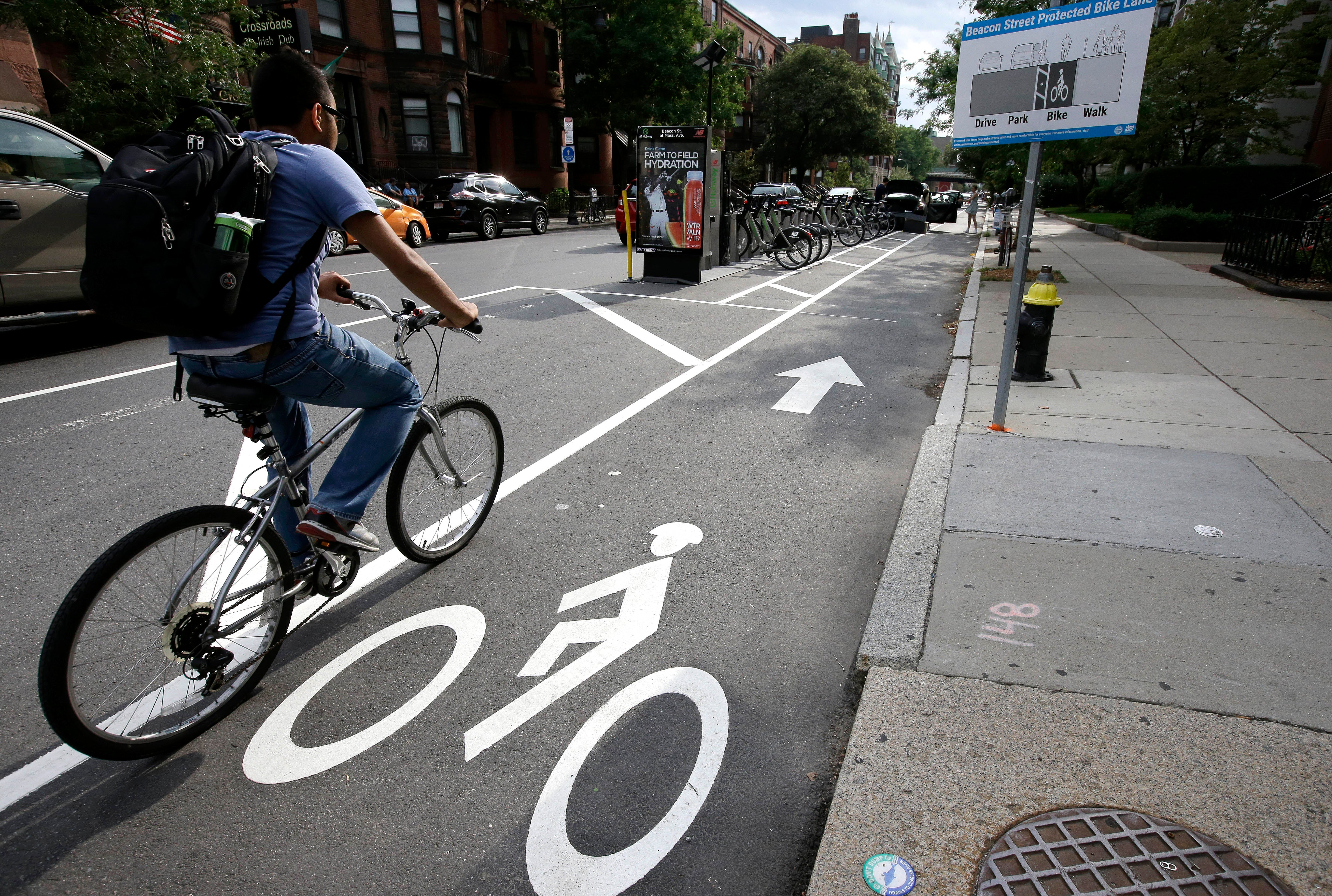 In this Tuesday, Aug. 16, 2016, photo, a cyclist enters a bike lane that is routed between parked cars and the sidewalk in Boston. Cities around the world are increasingly changing bike lanes to make them safer in light of fatal crashes involving cyclists and cars. (AP Photo/Steven Senne)