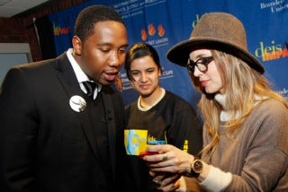 Actress Eliza Dushku shares something on her cell phone with Sneha Walia, center, a Brandeis student, and Ndaba Mandela before Ndaba and Kweku Mandela-Amuah, two grandsons of Nelson Mandela, spoke at Brandeis's annual festival of social justice. (07names - Mandelas and Dushkus at Brandeis. (Mike Lovett/Brandeis)