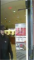 A surveillance camera photo of the Brim Beanie Bandit during one of his earlier capers.